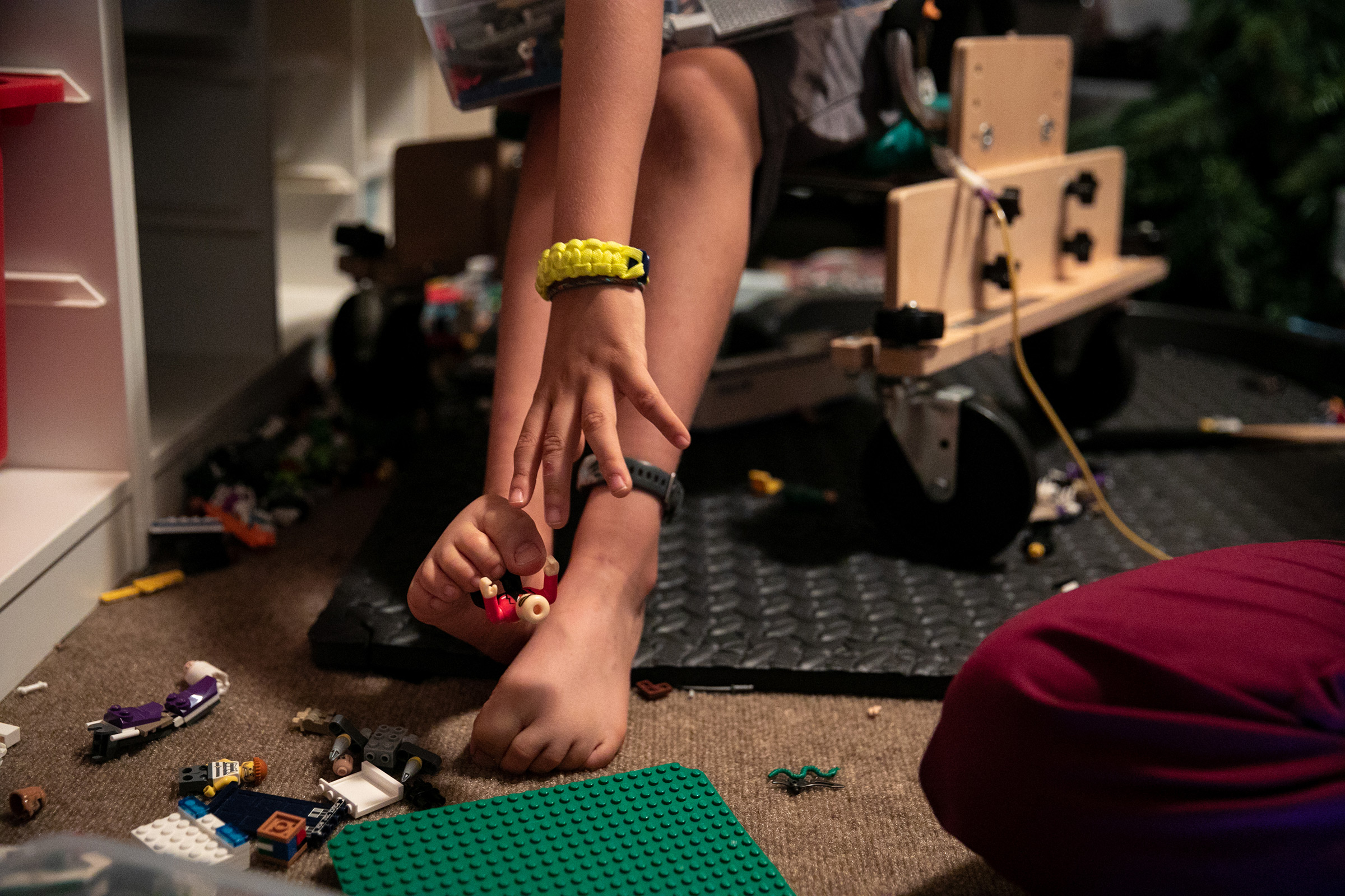Braden uses his toes to reach for a LEGO on a break inbetween physical therapy treatments.