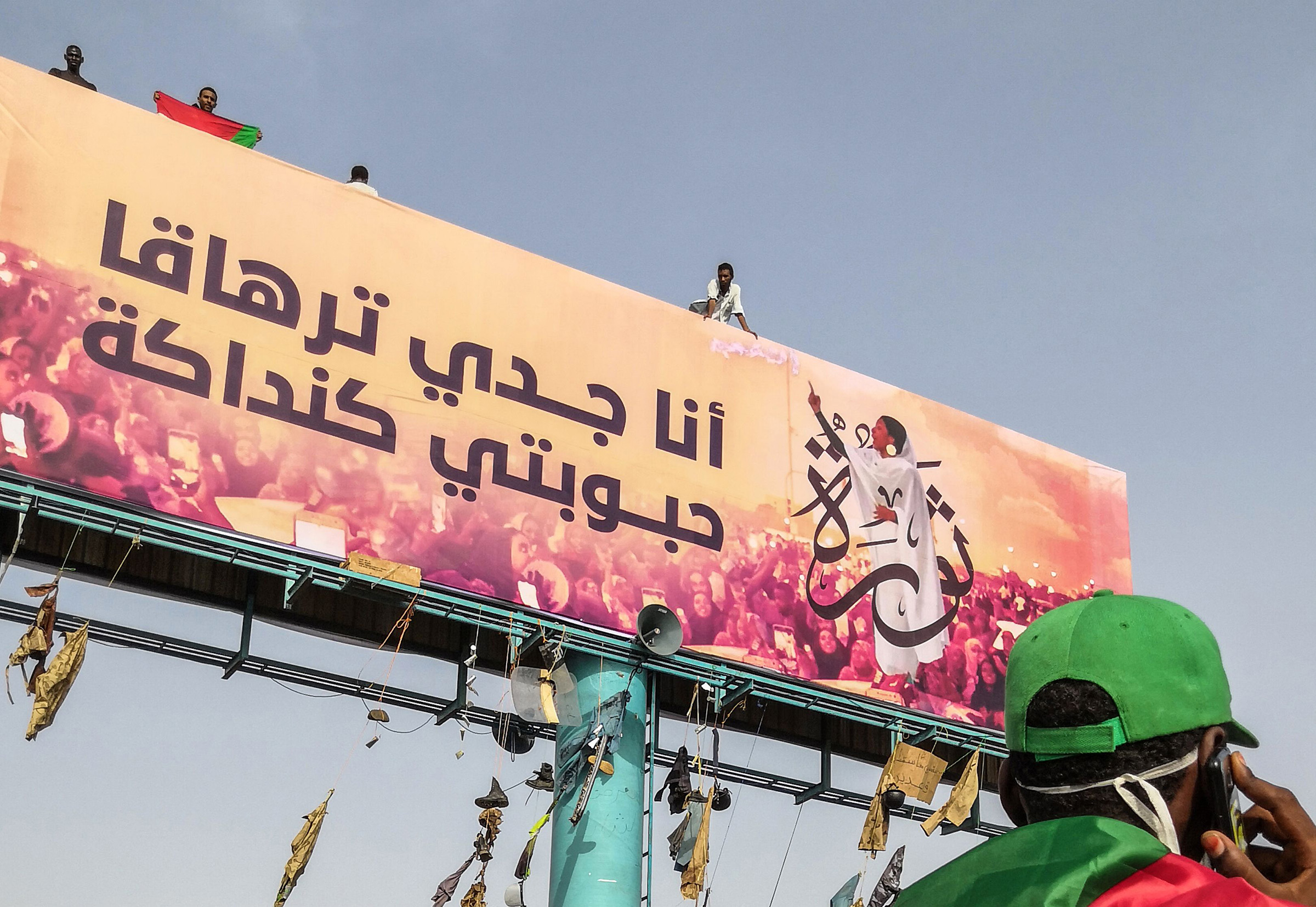 A Sudanese anti-regime protester speaks on his mobile telephone in Khartoum as he walks past a huge billboard bearing an image of Alaa Salah on on April 11, 2019.