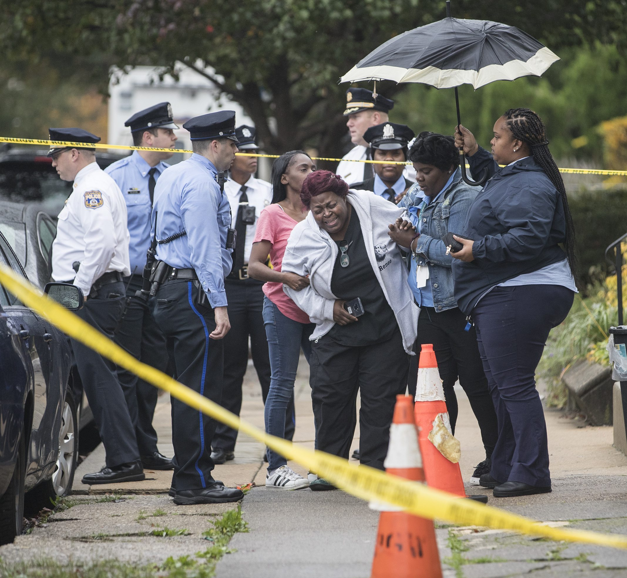 A grieving woman is assisted outside a home where four people were found shot dead on Oct. 30, 2019, in west Philadelphia.
