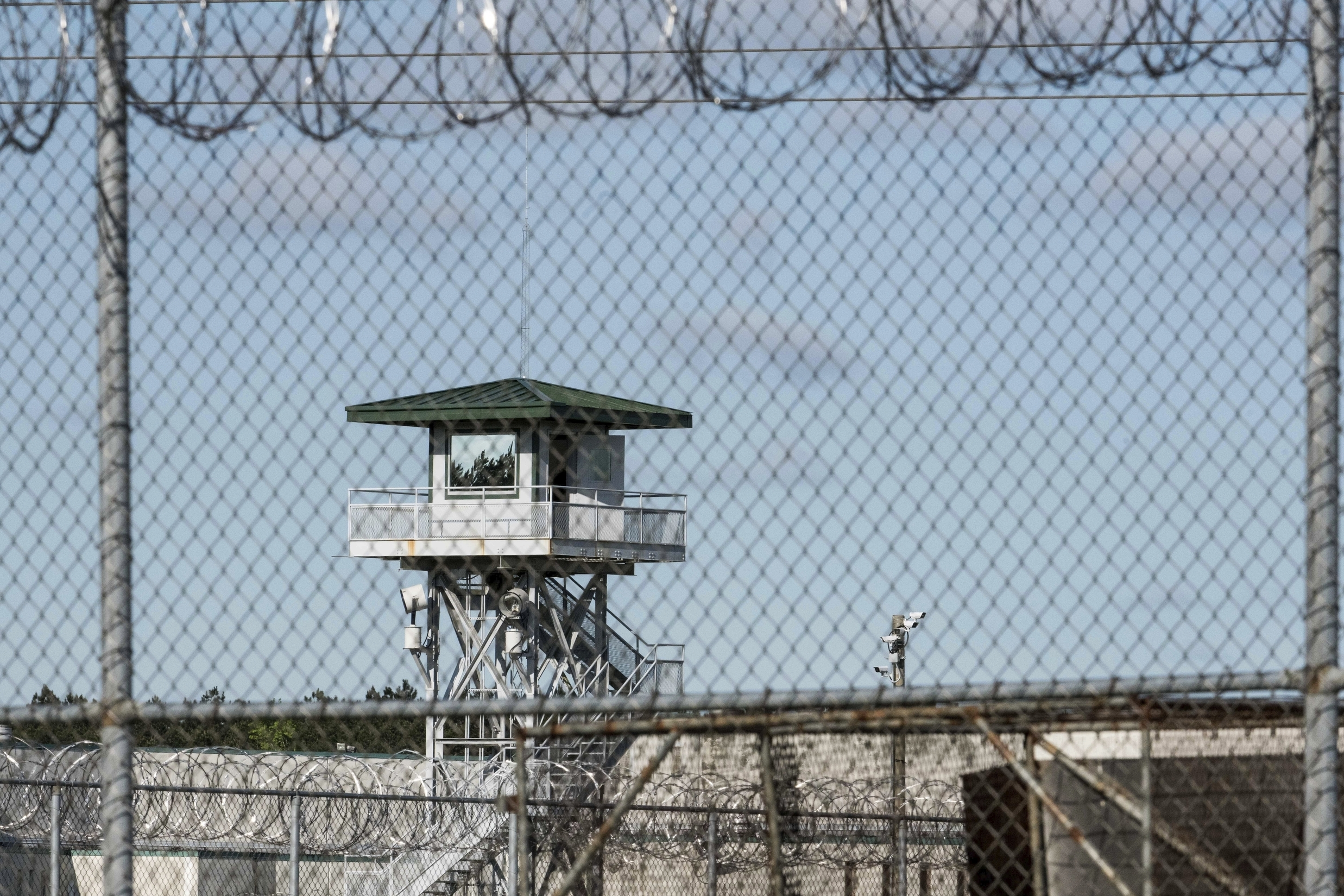 FILE - In this April 16, 2018, file photo, a guard tower stands above the Lee Correctional Institution, a maximum security prison in Bishopville, S.C., the morning after severl inmates were killed amid fighting among prisoners. South Carolina officials hope they can combat the dangers of illegal cellphones behind bars by providing inmates with a different kind of technological device. Corrections Director Bryan Stirling tells The Associated Press Thursday, Jan. 17, 2019, he's going to start handing out tablet computers that inmates can use for calling family members, watching movies and studying educational materials.  (AP Photo/Sean Rayford, File)