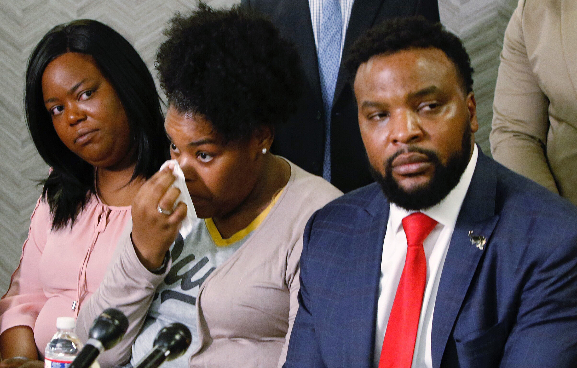 Amber Carr, center, wipes a tear as her sister, Ashley Carr, left, and attorney Lee Merritt, right, listen to Amber and Ashley's brother Adarius Carr talk about their sister Atatiana Jefferson during a news conference, Monday, Oct. 14, 2019, in downtown Dallas.