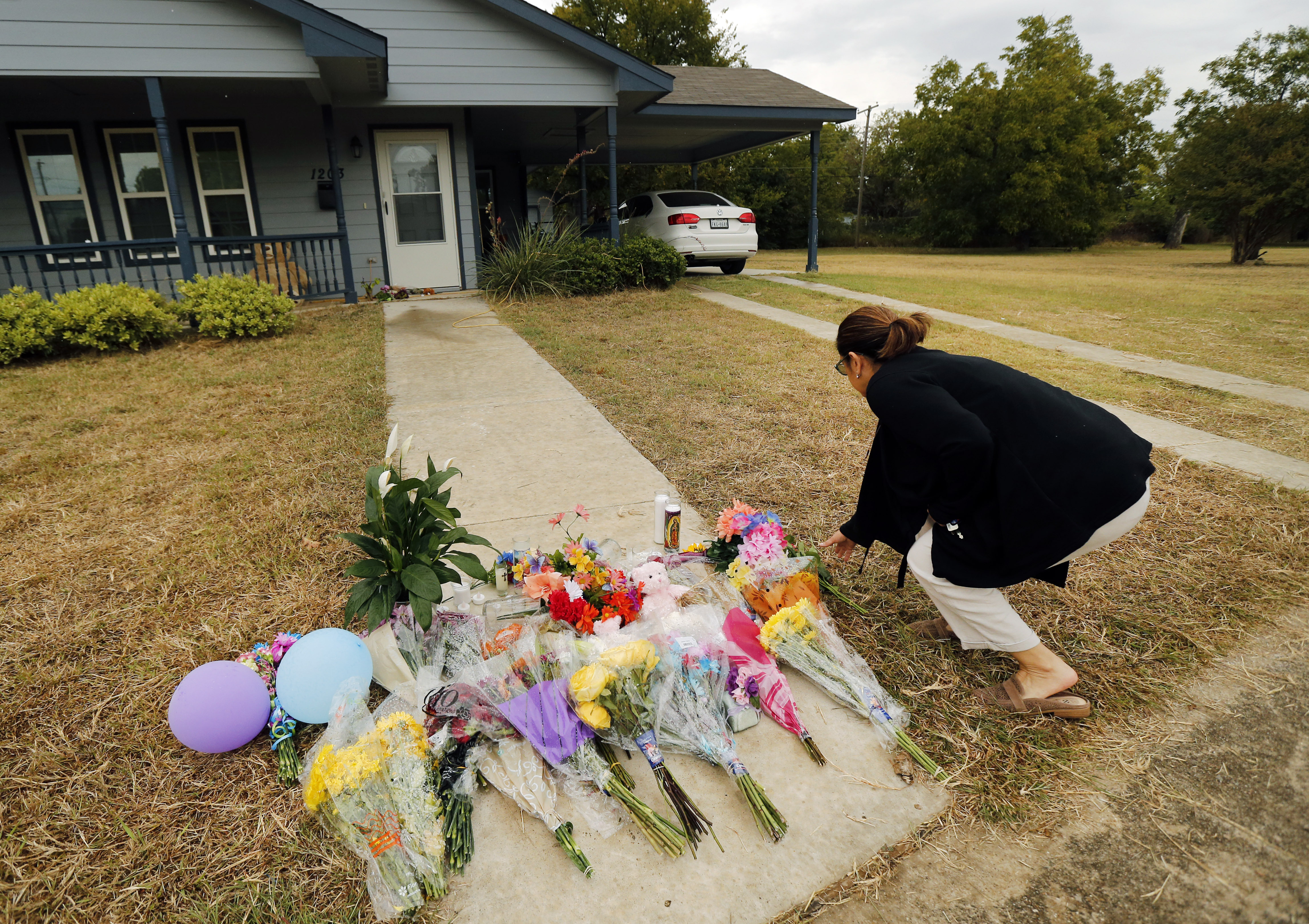 Anastasia Gonzalez, of Burleson, Texas, leaves a flowers on the front sidewalk of Atatiana Jefferson's home on E. Allen Ave in Fort Worth on Oct. 15, 2019.