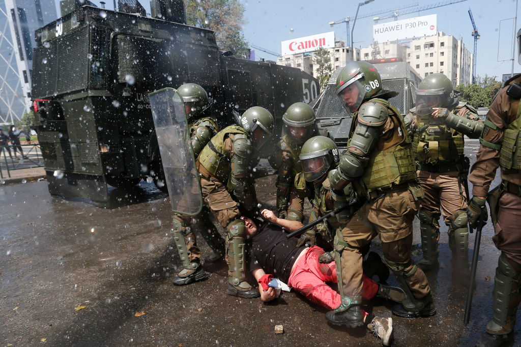 Protester is arrested by armed police in Santiago, Chile on Oct. 20, 2019