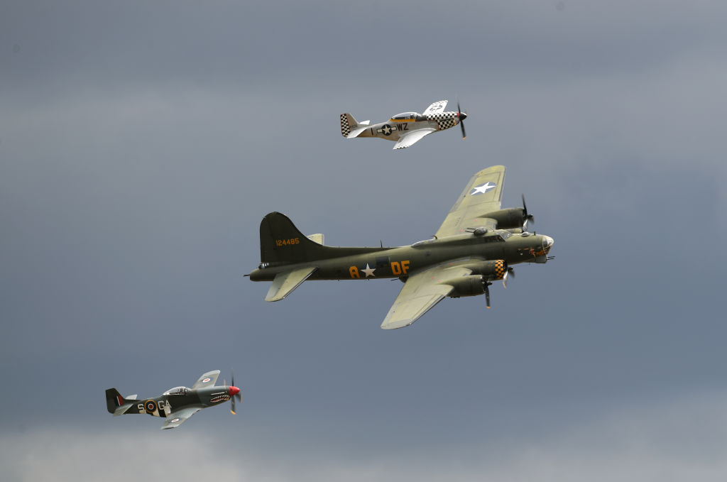 The U.K.'s last airworthy B-17 Flying Fortress, 'Sally B,' is flanked by a pair of P-51 Mustangs during the Flying Legends Air Show at IWM Duxford.