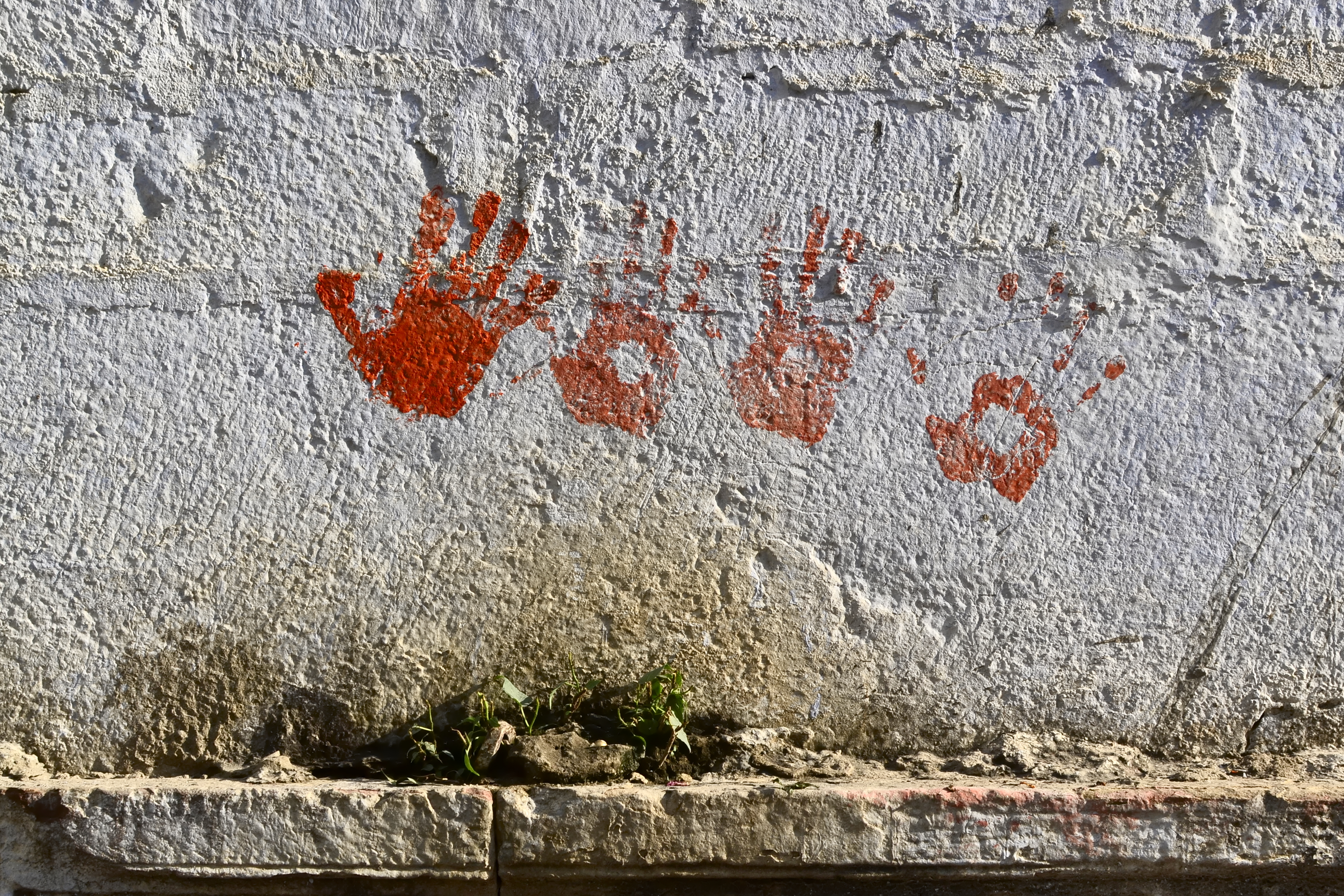 Red handprints on the white wall, Pushkar, Rajasthan, India