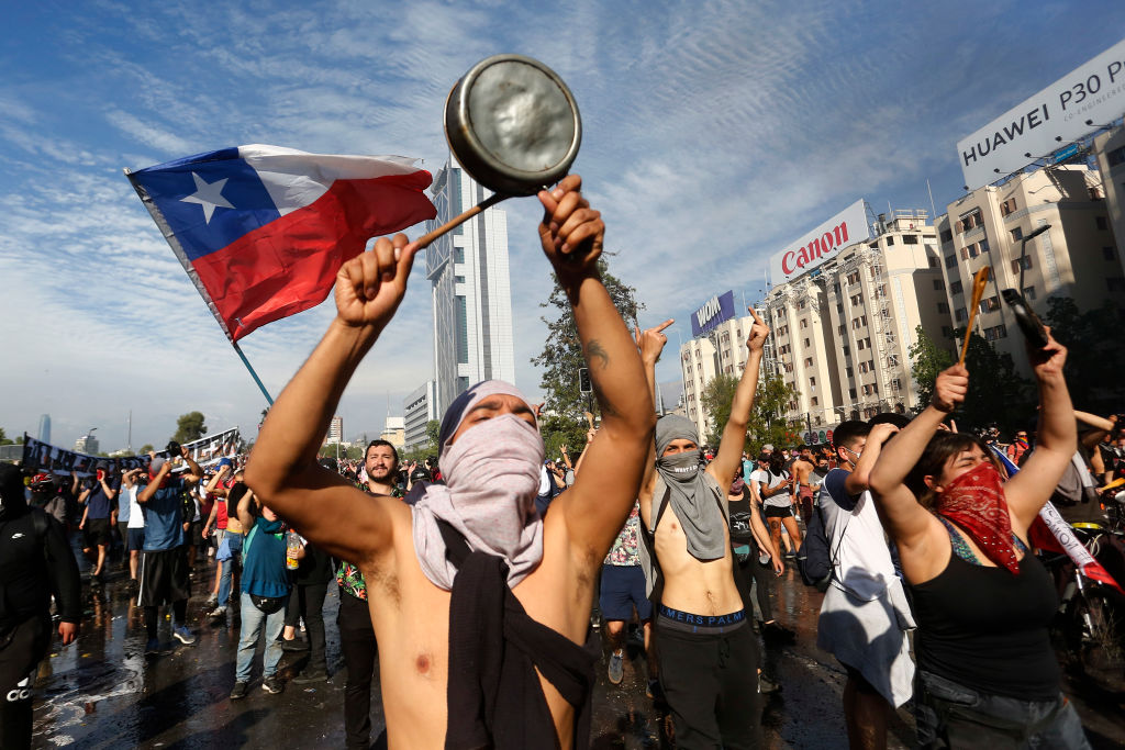Demonstrators display flags and banners during a protest against President Sebastian Piñera on Oct. 21, 2019 in Santiago, Chile, as protests continue into eighth day.