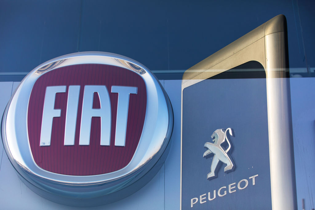 The logos of Fiat Chrysler Automobiles NV and Peugeot, a unit of PSA Group, sit on display in automobile showrooms in Dubai, United Arab Emirates, on Oct. 31, 2019.