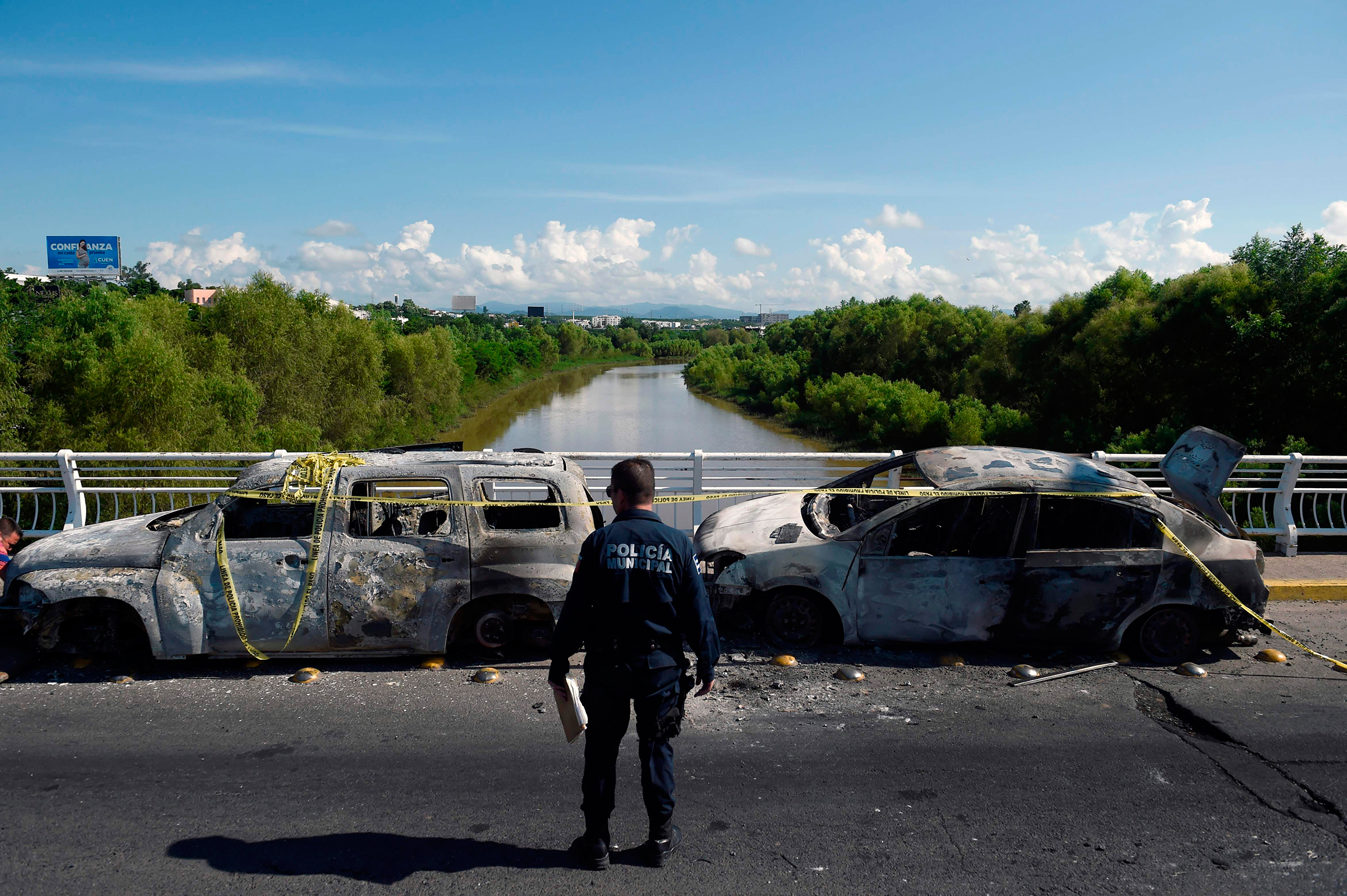 A policeman stands next to burnt vehicles after heavily armed gunmen had waged an all-out battle against Mexican security forces in Culiacan, Mexico.
