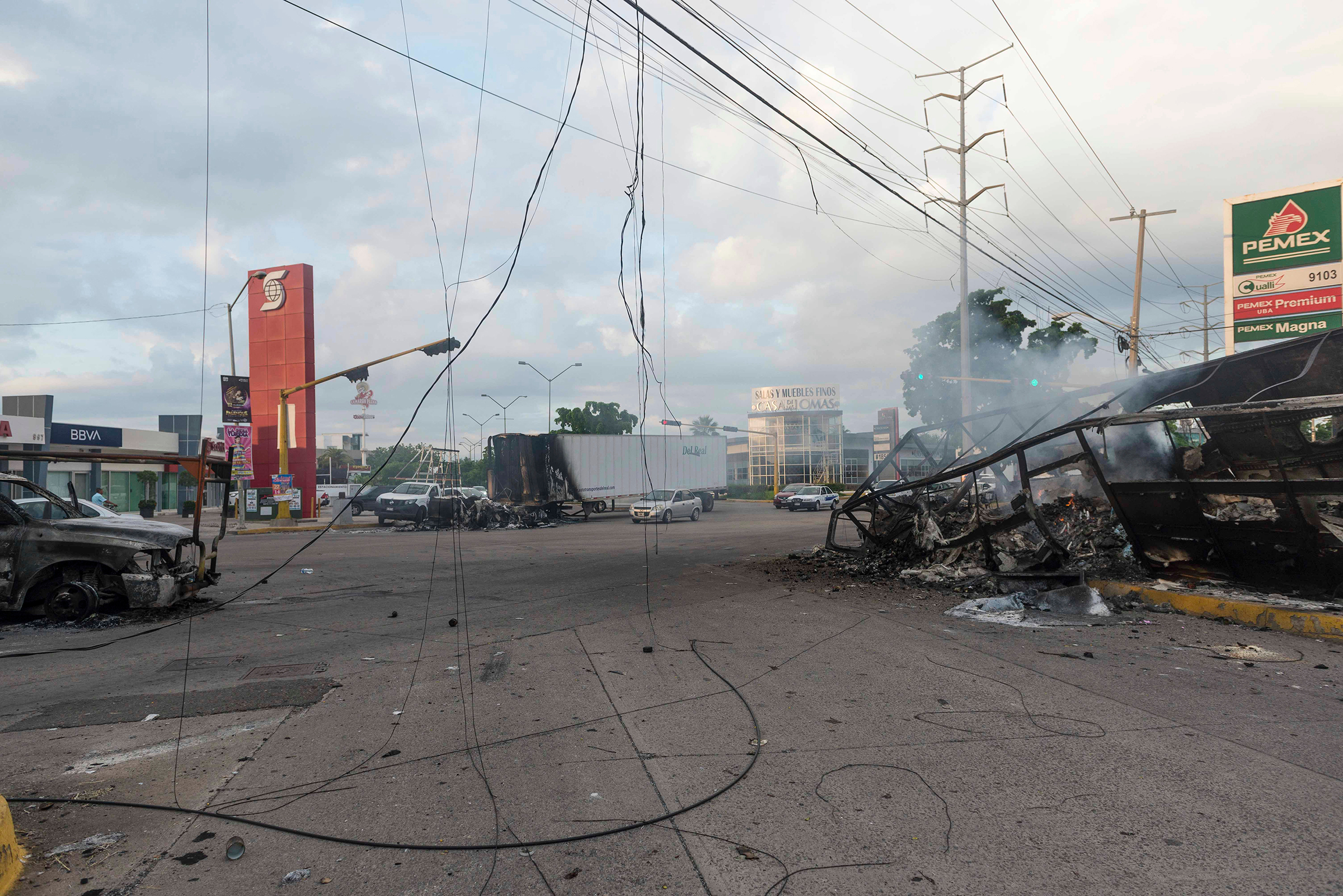 Burnt vehicles used by gunmen smolder on an intersection, one day after street battles with security forces, in Culiacan on Oct. 18.