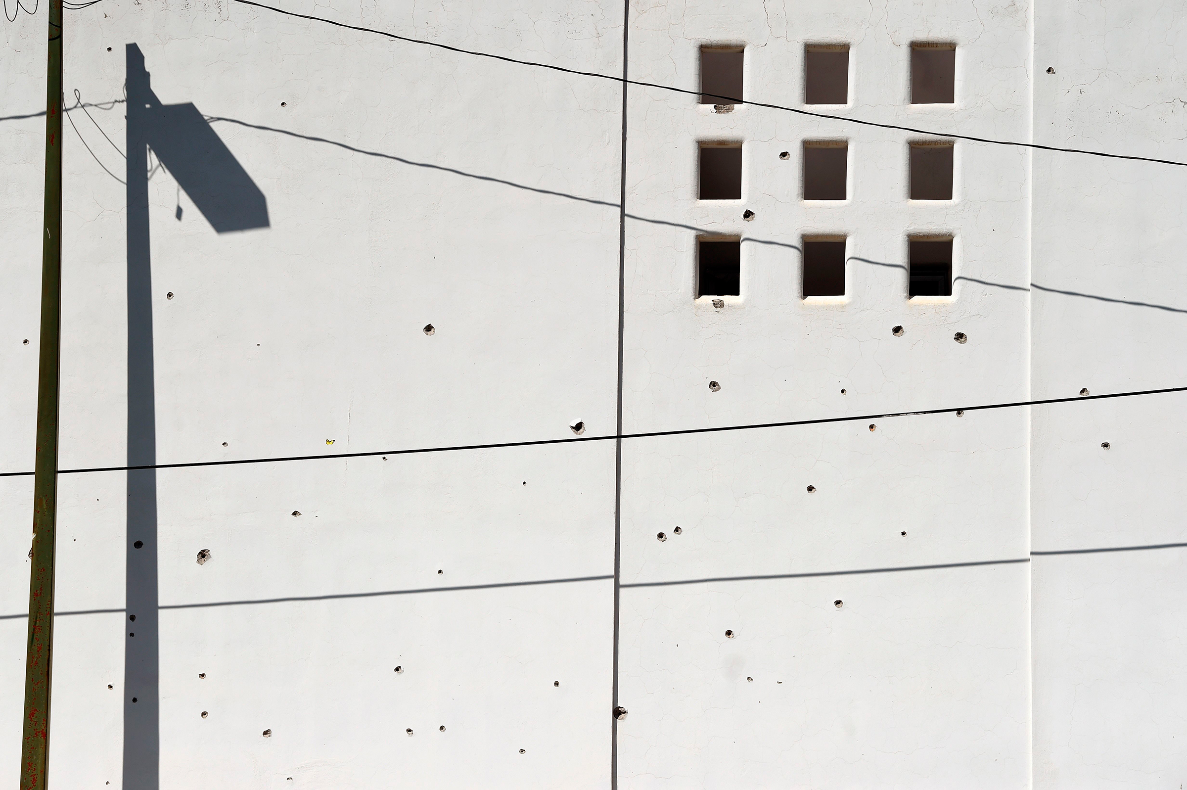 A wall is pockmarked with bullet holes in Culiacan on Oct. 18.
