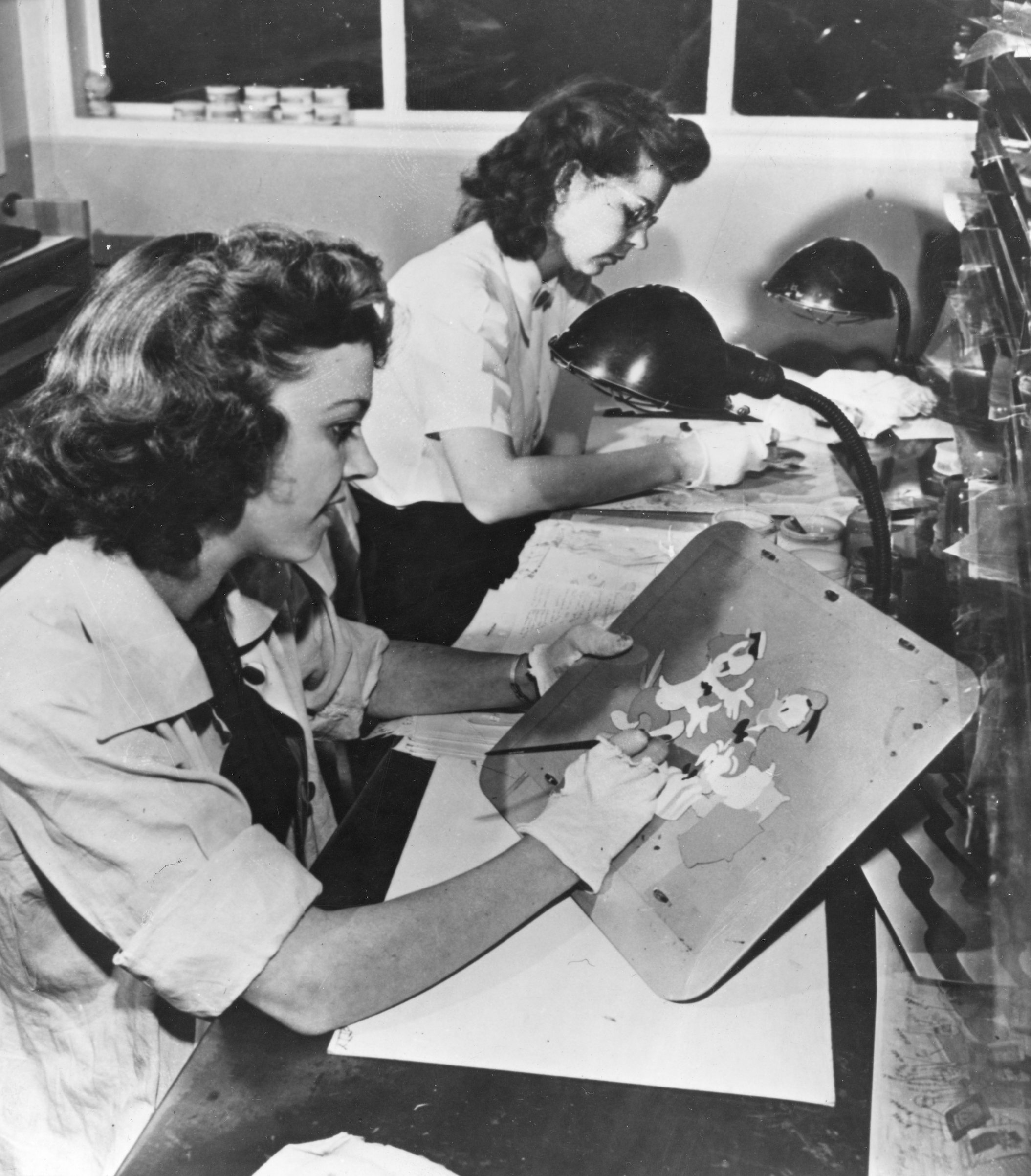 Two unidentified artists paint animation cels in Disney Studios' inking and painting department, Burbank, Calif., 1943.