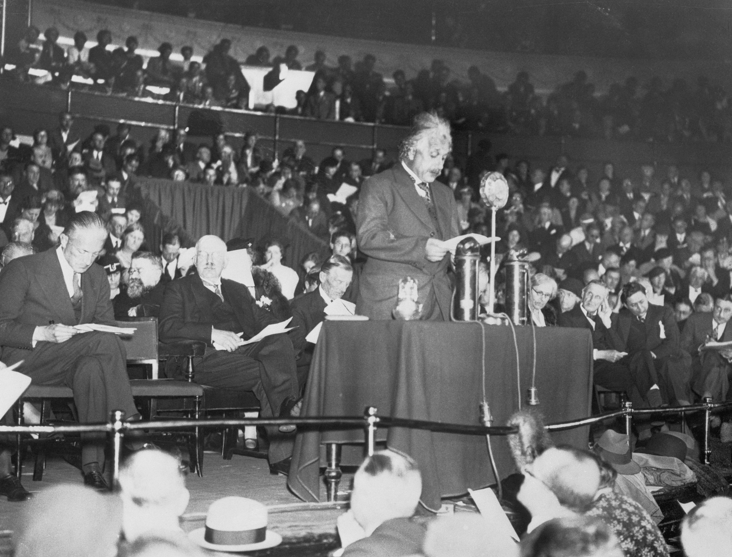 Professor Albert Einstein, who has taken up residence in England as a refugee from Nazi threats, was among the prominent speakers who addressed a great gathering at the Royal Albert Hall in London, recently, to aid the Jewish Refugee Fund. Commander Locker Lampson, M.P., Lord Rutherford and Sir Austen Chamberlain were among the principal speakers of the meeting. Photo shows Professor Einstein during the delivery of his speech. October 1933.