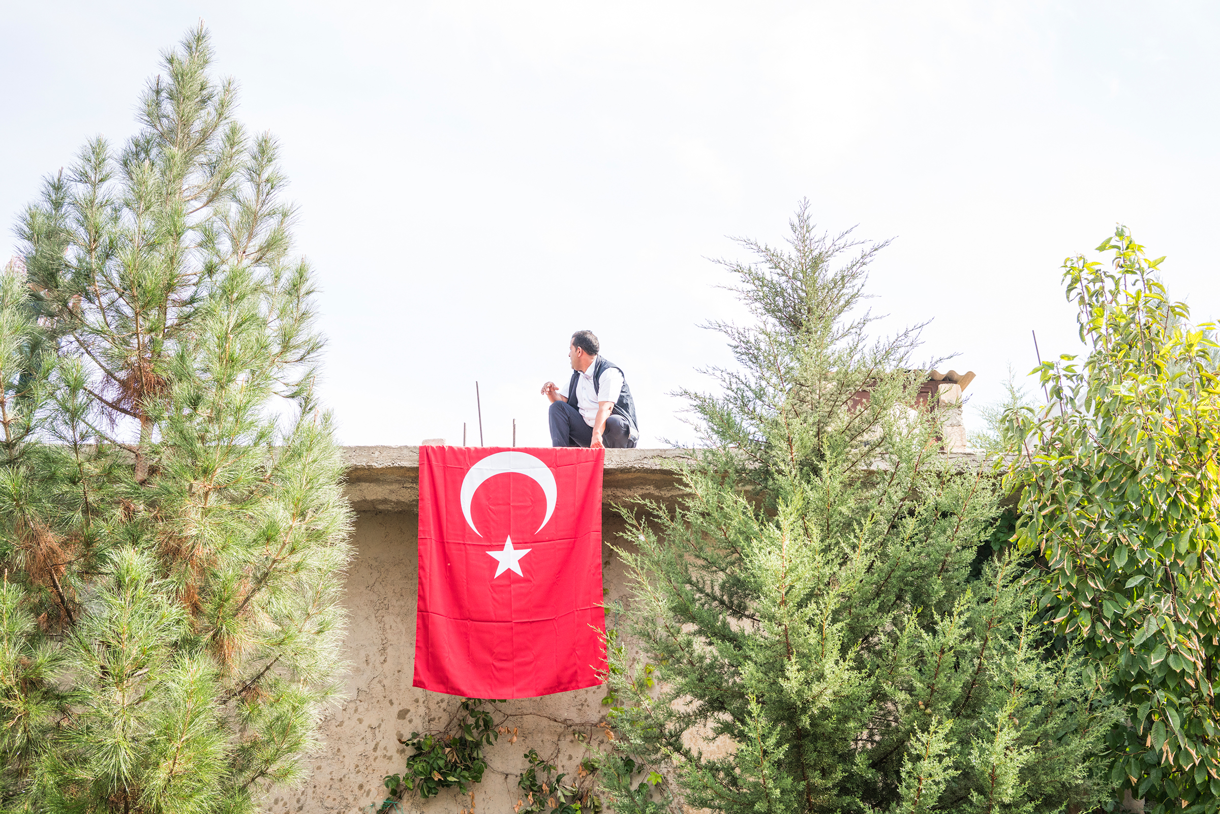 A man places a Turkish flag in the courtyard of a mosque before the funeral of a nine-month-old Syrian baby, who was killed during rocket and mortar attacks in Akçakale, Turkey, on Oct. 11, 2019.