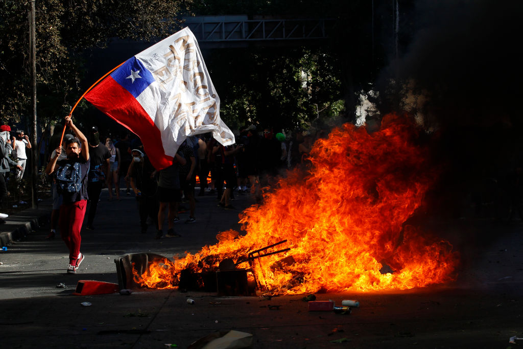 A demonstrator waves a Chilean flag next to a fire as clashing with riot police during a protest against President Sebastian Piñera on Oct. 21, 2019 in Santiago, Chile.