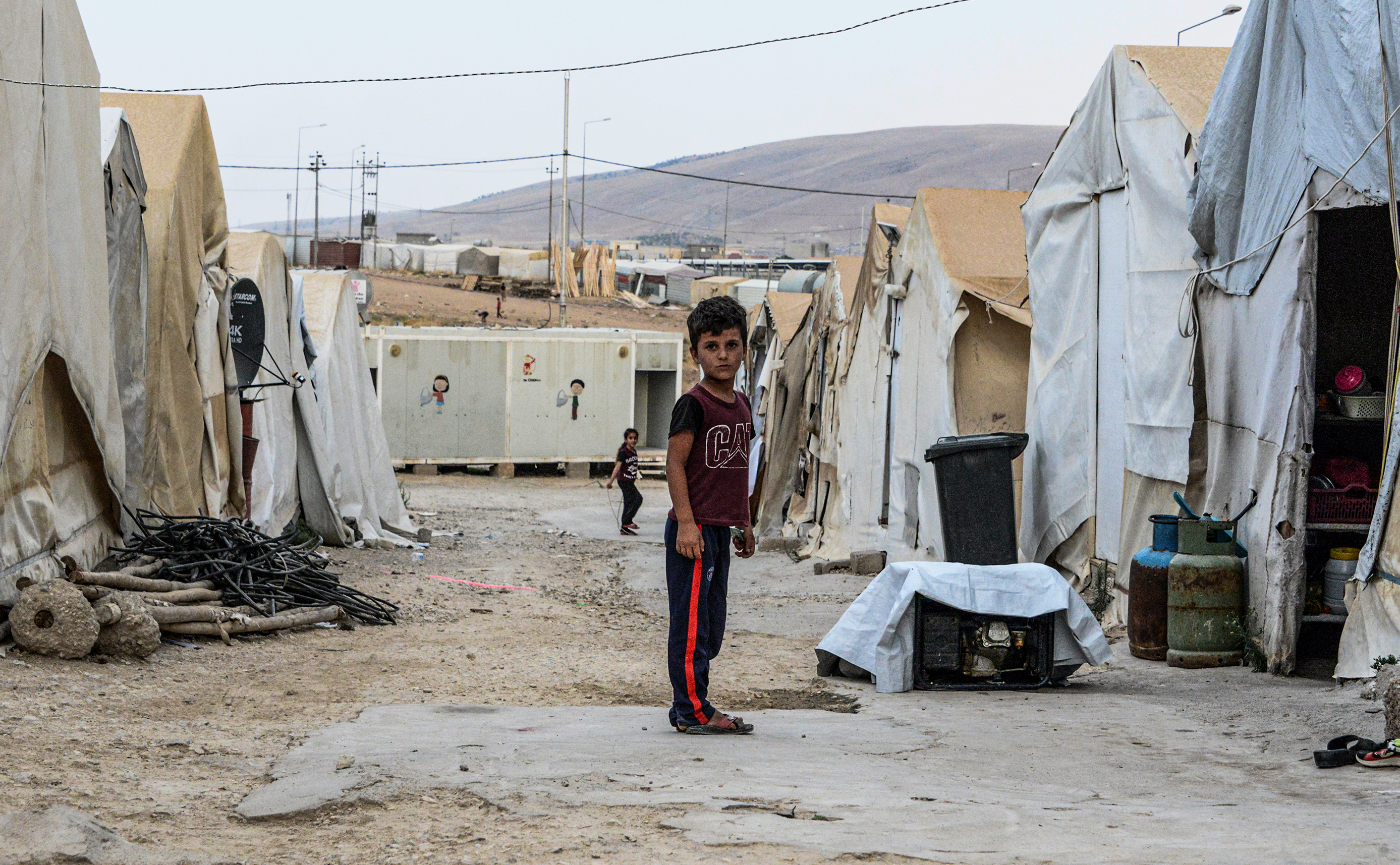 A boy stands between tents at a camp for internally displaced persons (IDP) of Iraq's Yazidi minority in the Sharya area, some 15 kilometres from the northern city of Dohuk in the autonomous Iraqi Kurdistan region on August 30, 2019.