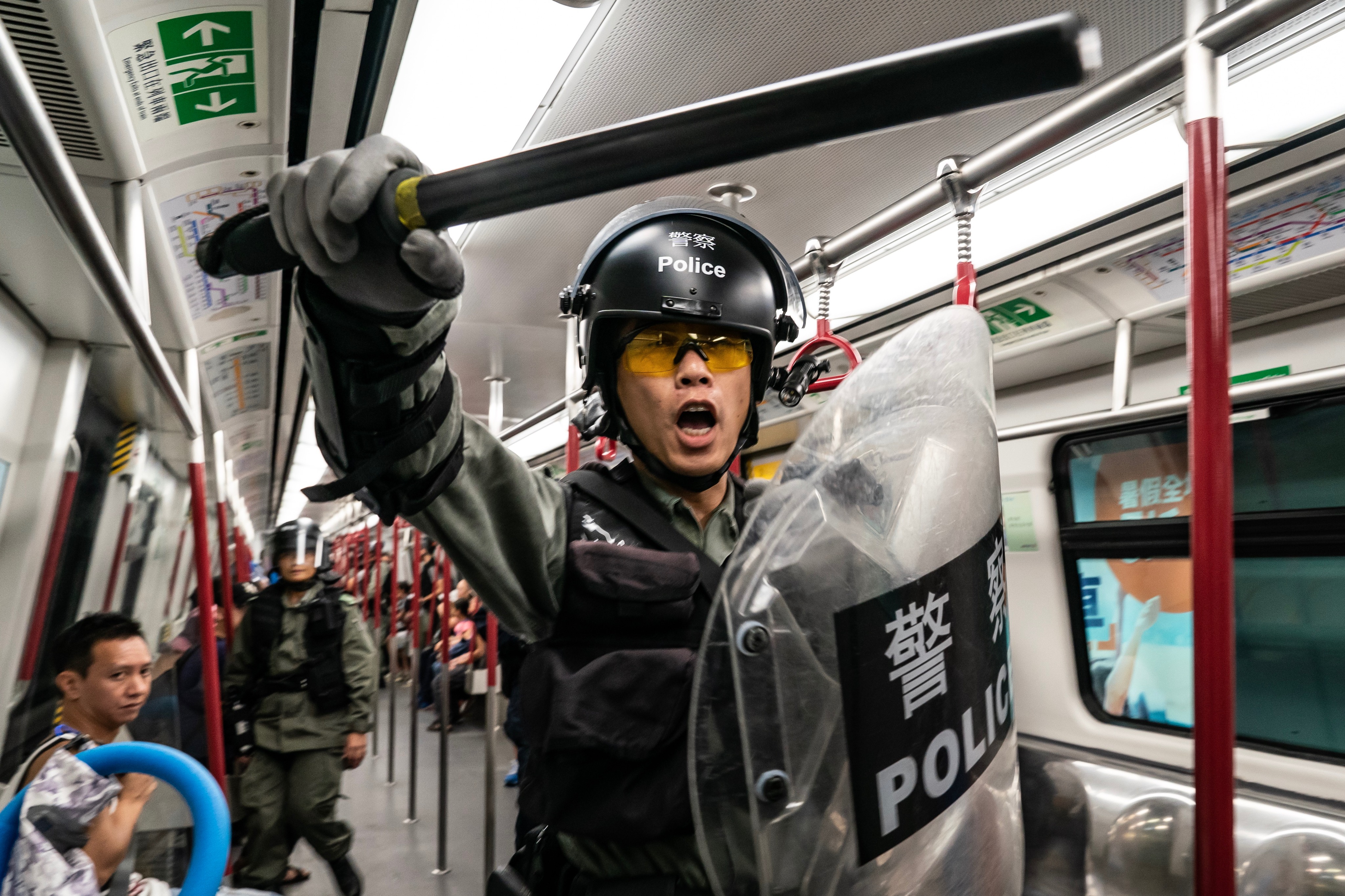 Riot police charge in a train at the Tung Chung MTR station after protesters block the transport routes to Hong Kong International Airport on September 1, 2019 in Hong Kong, China.