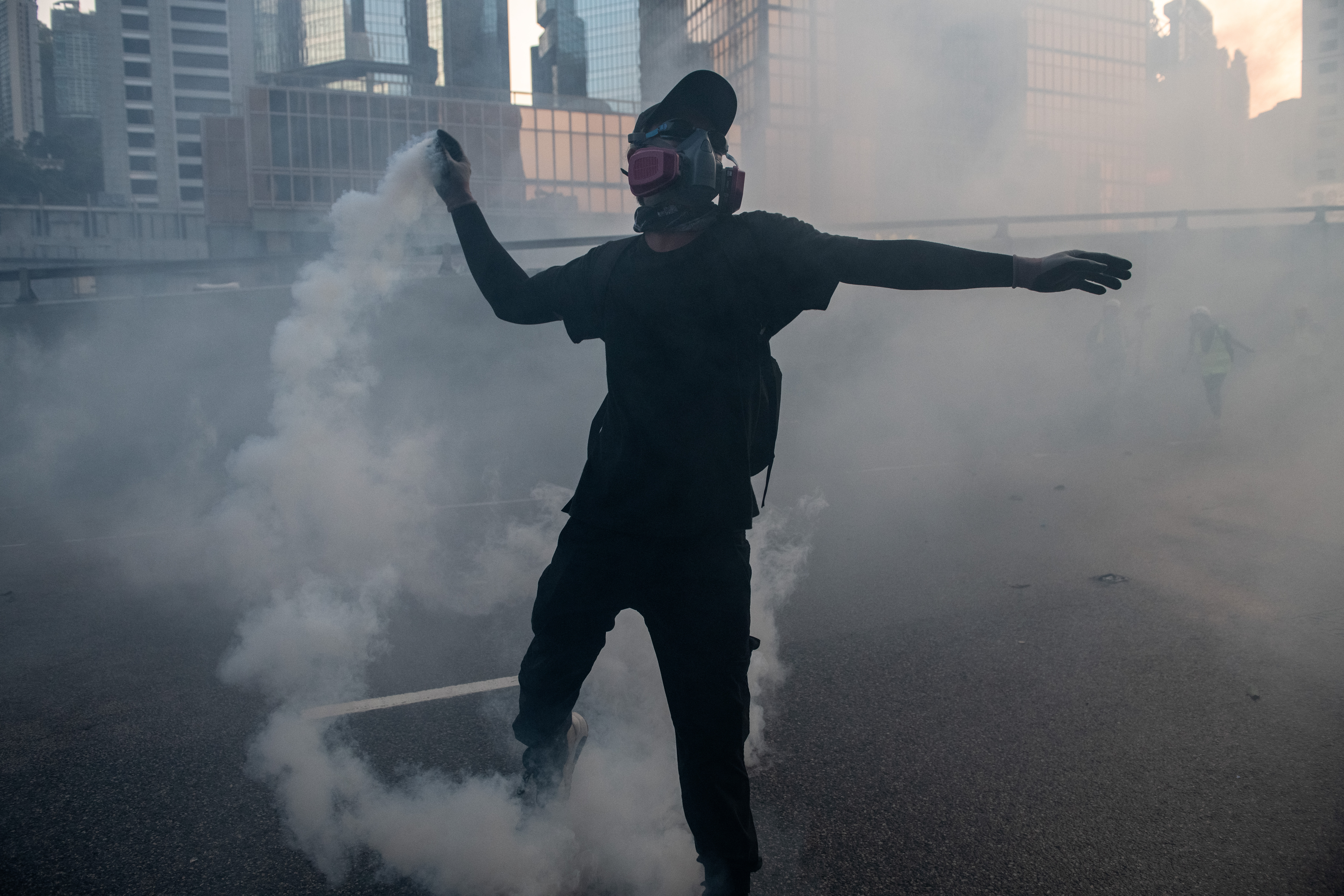 A pro-democracy protester throws a police teargas cartridge back at police officers in the Central Government Offices on September 15, 2019 in Hong Kong, China.