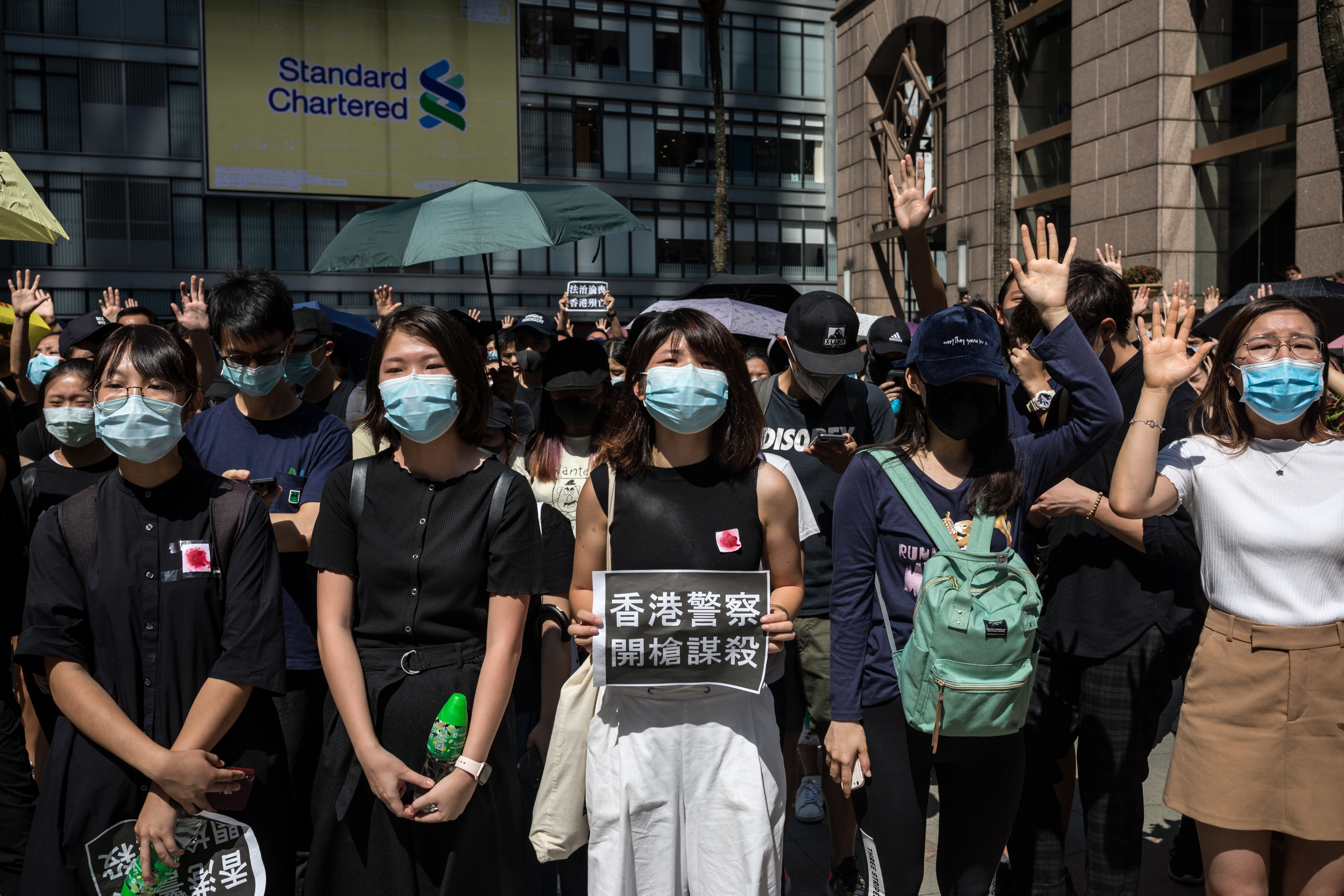 A demonstrator holds a sign with Chinese characters reading  Hong Kong Police, Murder With Gunfire  as other protesters gesture  Five Demands  during a flash mob in the Sheung Wan district of Hong Kong, China, on Wednesday, Oct. 2, 2019.