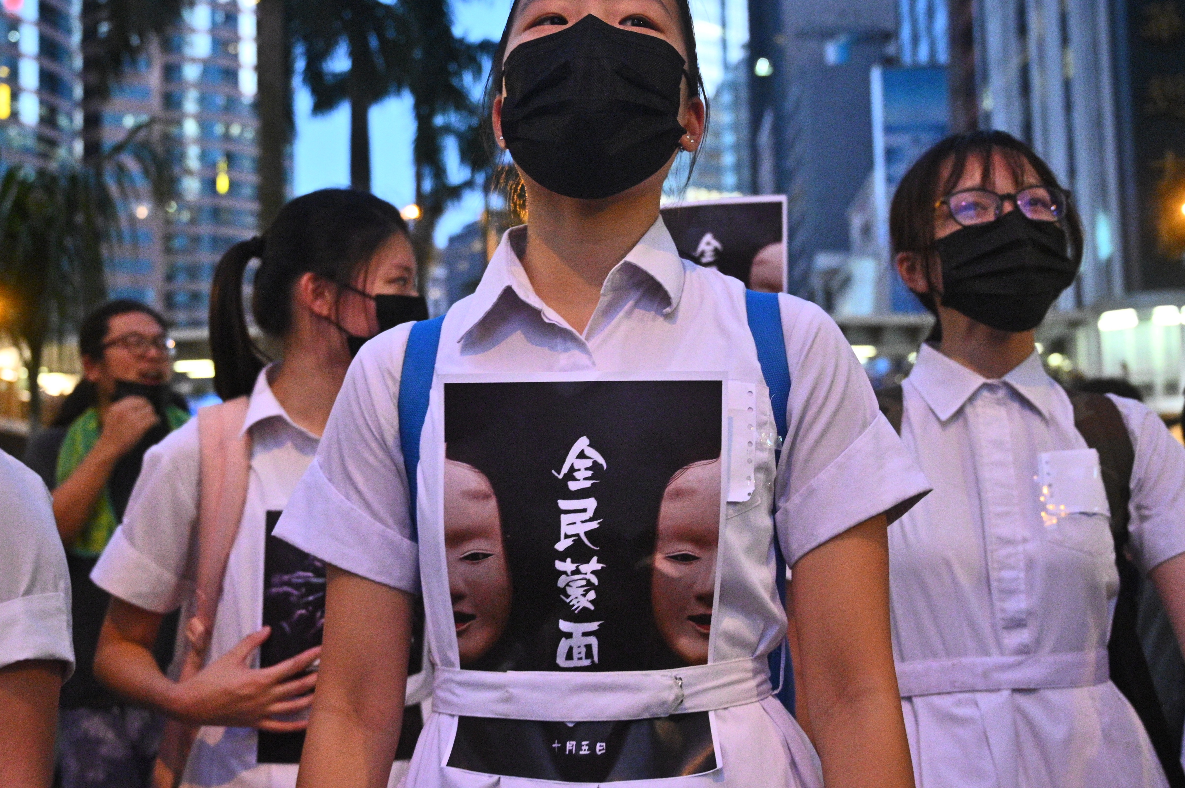 High school students chant slogans as they stick posters reading  all people masked  on their uniforms while protesters gather in the heart of Hong Kong's commercial district Central on October 4, 2019, after the government announced a ban on facemasks.