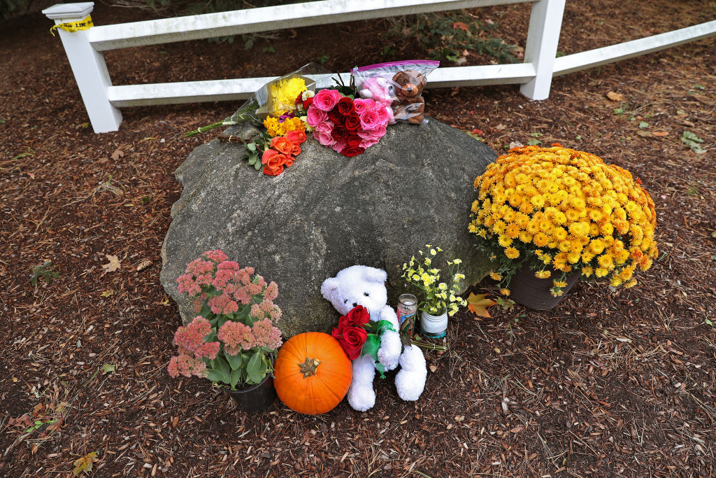 Flowers, pumpkins and stuffed animals are placed outside the Zaccardi family home in Abington, MA on Oct. 8, 2019. One day after a couple and their three young children were found dead here in their home, the crime scene still bore remnants of the unspeakable tragedy as residents wore green to honor the victims. A memorial of flowers, stuffed animals and a single candle was visible Tuesday outside the Centre Avenue condo complex where the victims were found dead from gunshot wounds.