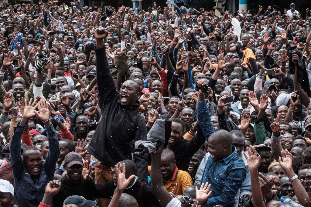 Kenyans watch a big screen on October 12, 2019, in Nairobi as they celebrate Kenya's Eliud Kipchoge victory.
