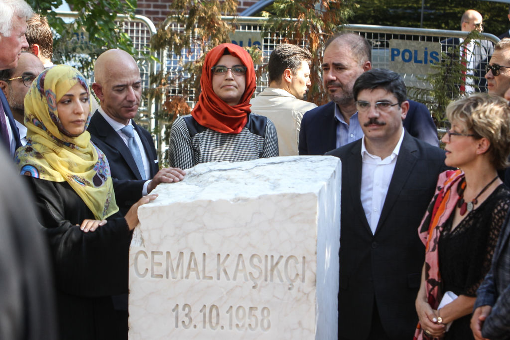 Hatice Cengiz (C), the fiancee of murdered Saudi journalist Jamal Khashoggi, CEO of Amazon and Washington Post owner Jeff Bezos (2nd L), and participants stand near by a memorial stone during an event marking the one-year anniversary of the assassination of Saudi dissident journalist Jamal Khashoggi on October 02, 2019 in Istanbul, Turkey