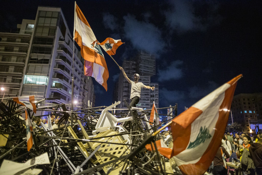 An anti-government protester waves a Lebanese flag as he stands on top of a pile of broken tents in Martyrs' Square on Oct. 29, 2019 in Beirut, Lebanon, following the resignation of Lebanese Prime Minister Saad Hariri