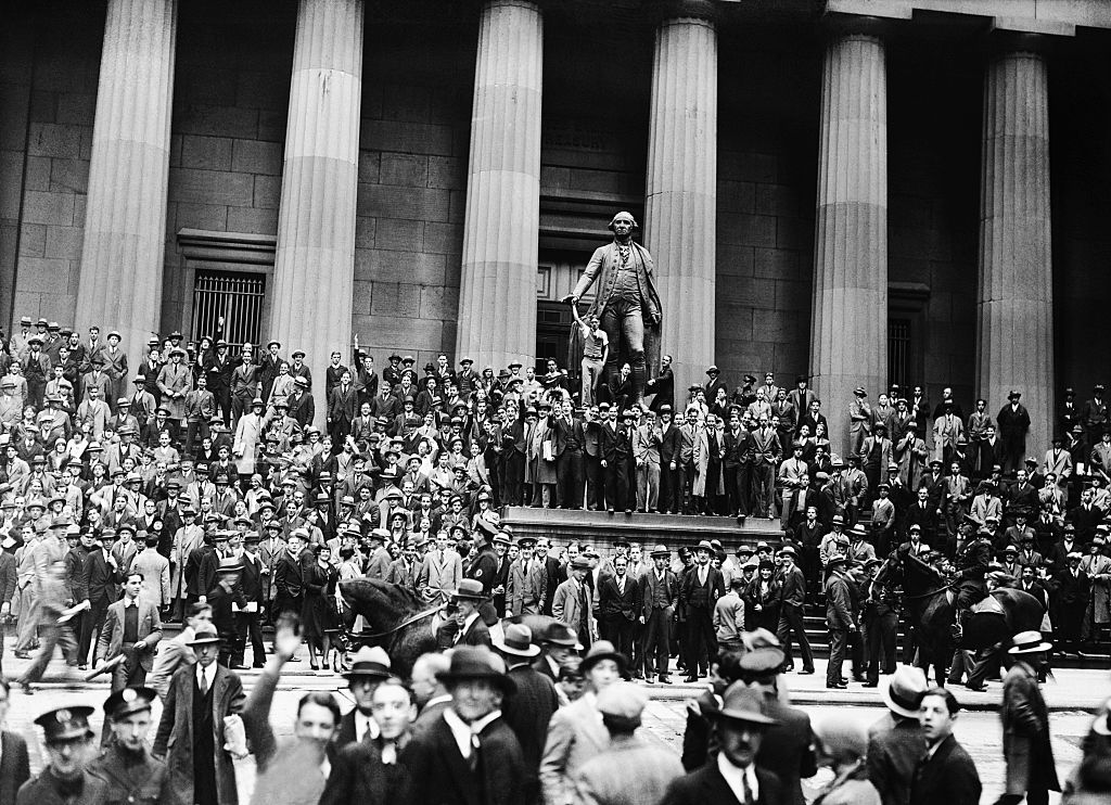Crowds gather around a statue of the first U.S. President George Washington about a block from the New York Stock Exchange on Black Thursday, Oct. 24, 1929.