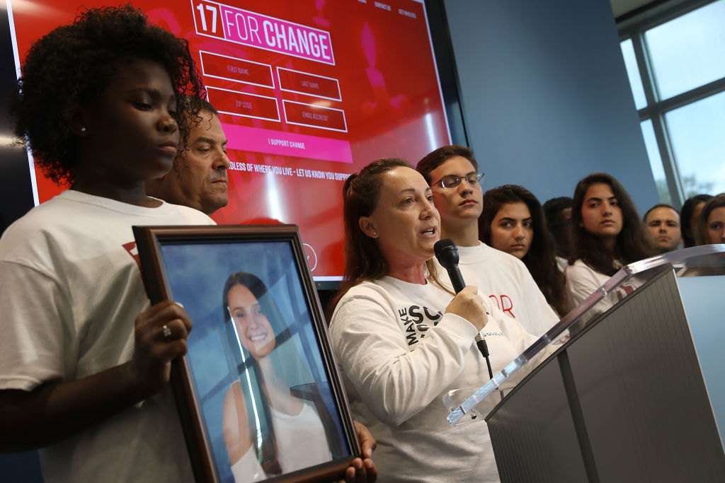 Lori Alhadeff, whose daughter Alyssa was one of 17 people killed in the shooting at Marjory Stoneman Douglas High School, speaks at a news conference in Coral Springs, Fla., on March 28, 2018, as Melia Rodriguez holds a picture of Alyssa.