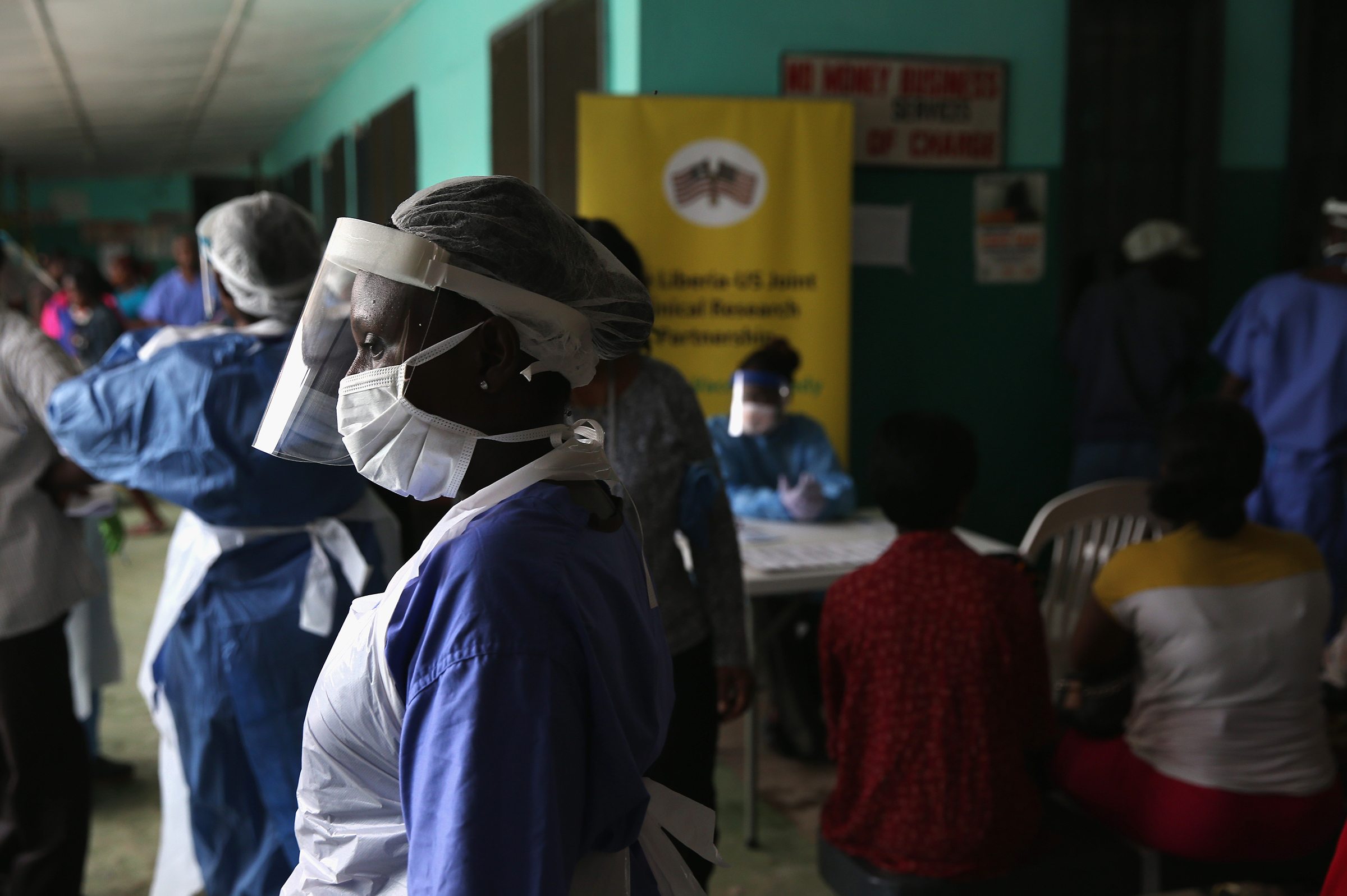Health workers in protective clothing await patients in the outpatient lounge of Redemption Hospital, formerly an Ebola holding center, on Feb. 2, 2015 in Monrovia, Liberia.