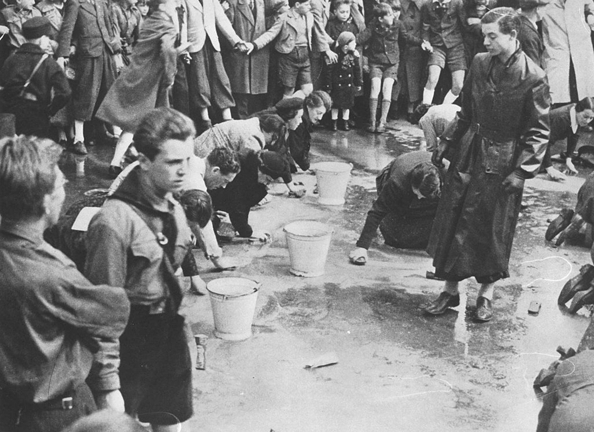 A 1938 photo of Hitler Youth members looking on as Jewish people were forced to scrub the streets in Vienna, Austria.