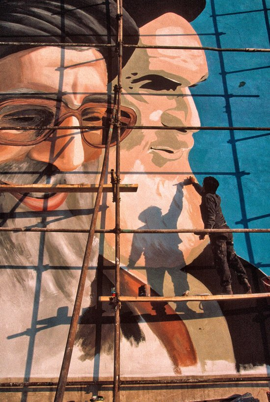 A painter works on a Tehran mural of Khamenei, left, and Iran's first Supreme Leader, Ruhollah Khomeini