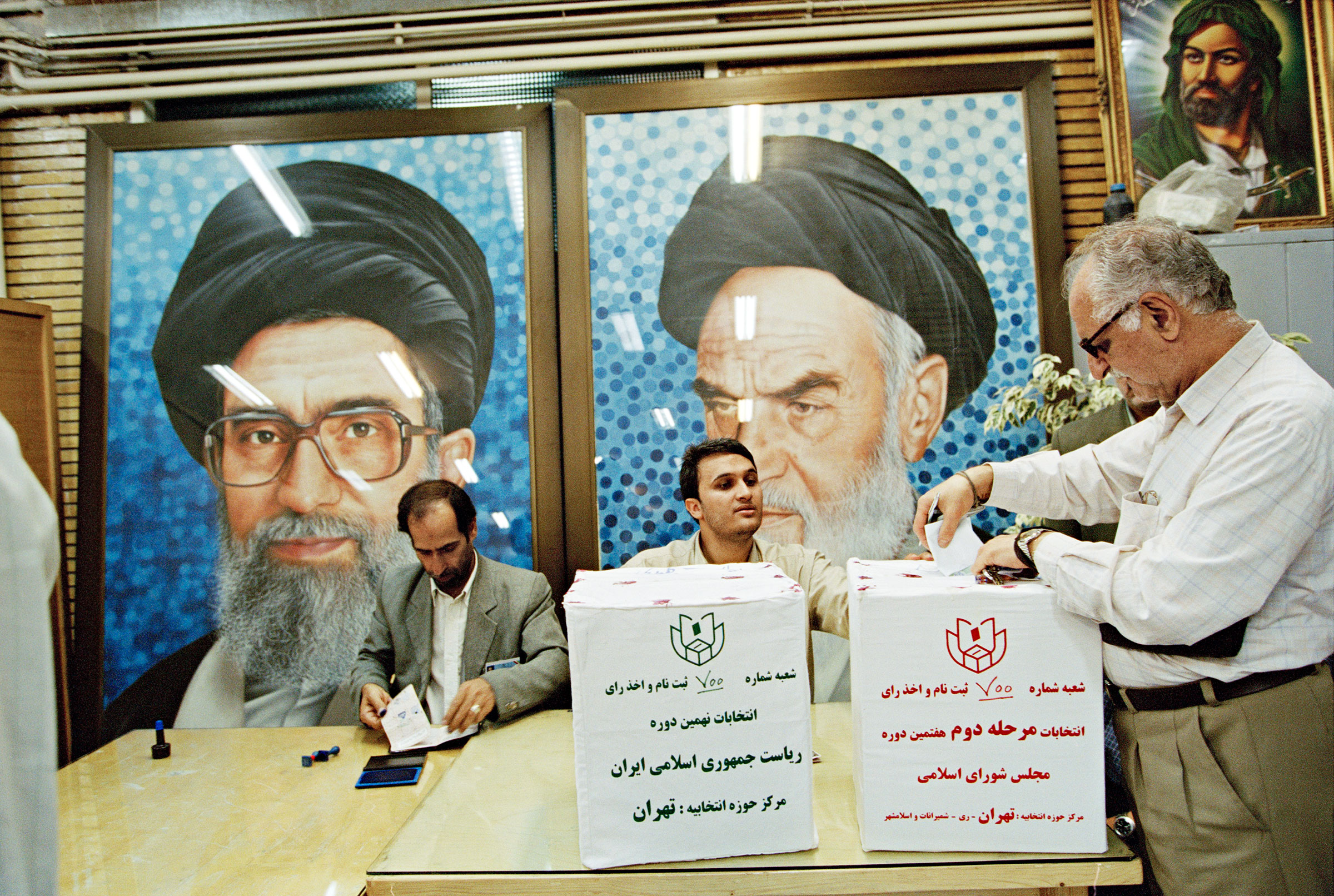 Portraits of Khamenei and his mentor and predecessor, Khomeini (right), at a Tehran polling place in June