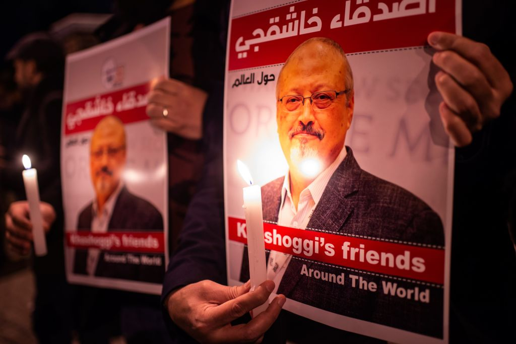 People hold posters picturing Saudi journalist Jamal Khashoggi and lightened candles during a gathering outside the Saudi Arabia consulate in Istanbul, on October 25, 2018.