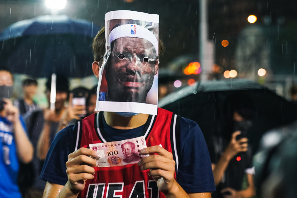 A basketball fan wearing a Miami Heat jersey with a LeBron James mask and a 100 Chinese yuan bill on October 15, 2019 in Southorn Playground, Wan Chai, Hong Kong, China.
