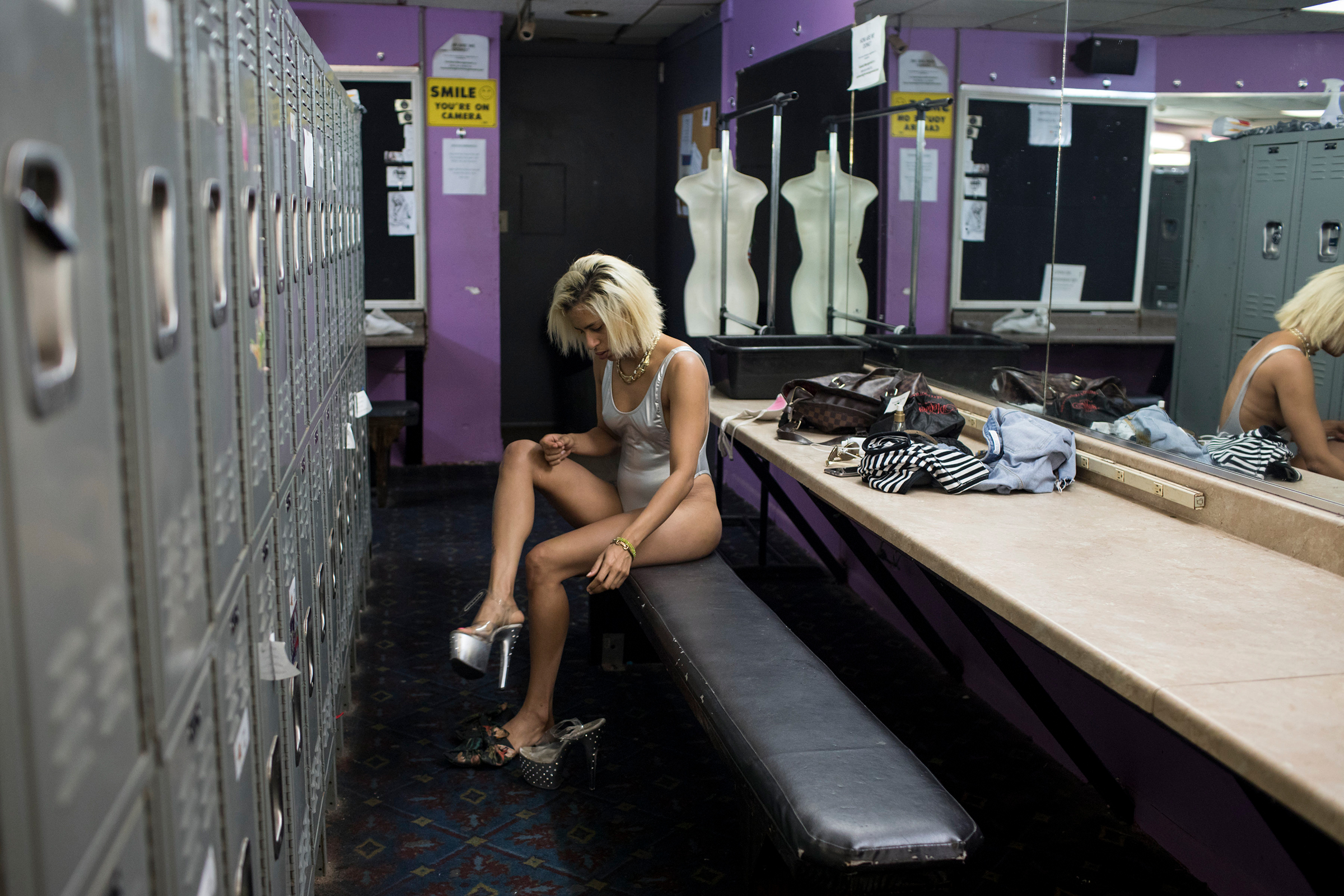 Liset prepares for work as a stripper in Austin. She works the day shift, texting her regular clients to come see her when she's working. She says they enjoy her company and she knows how to make them feel special.