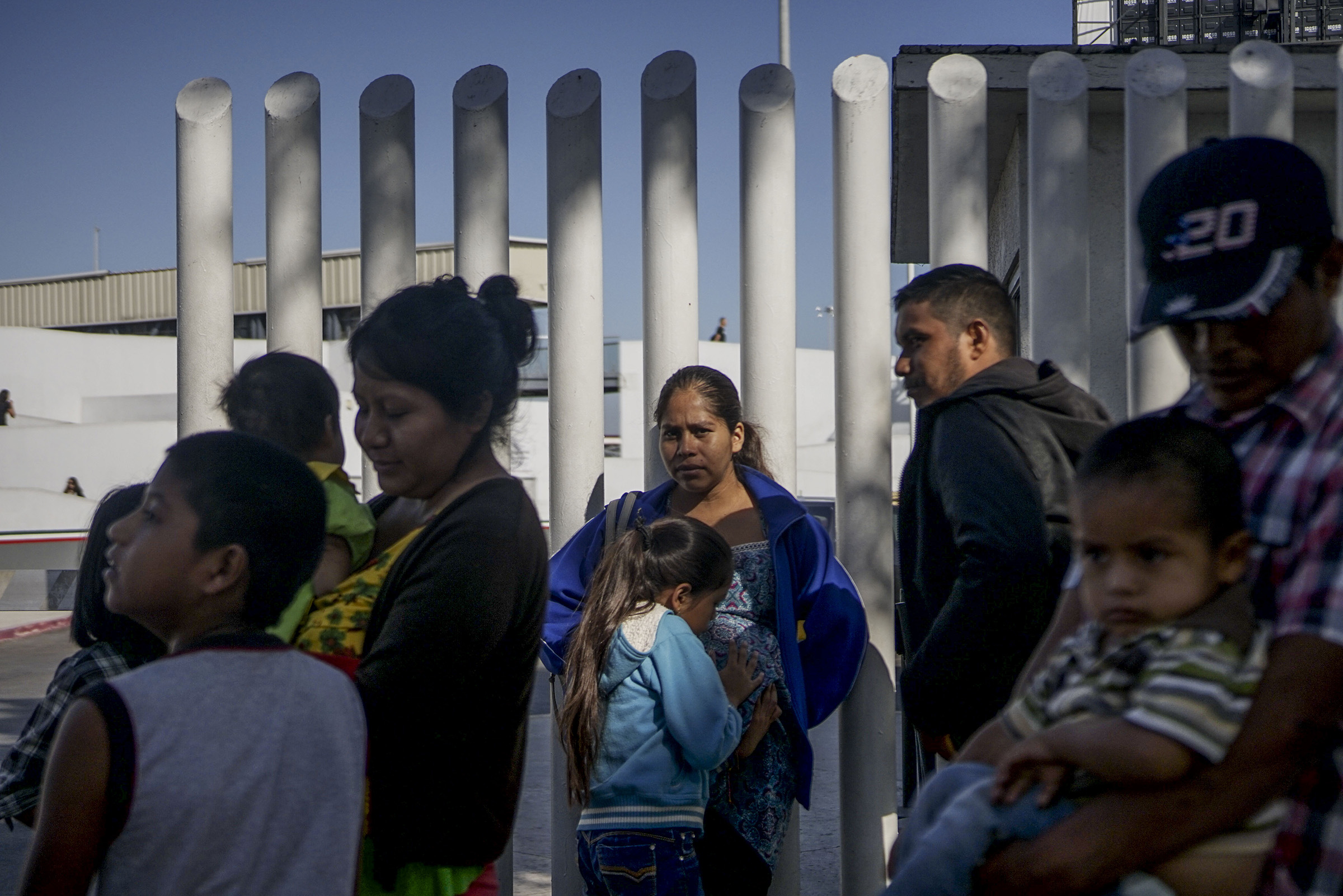 Migrants wait in line at the Mexico-United States border crossing in Tijuana, Mexico on September 12, 2019.