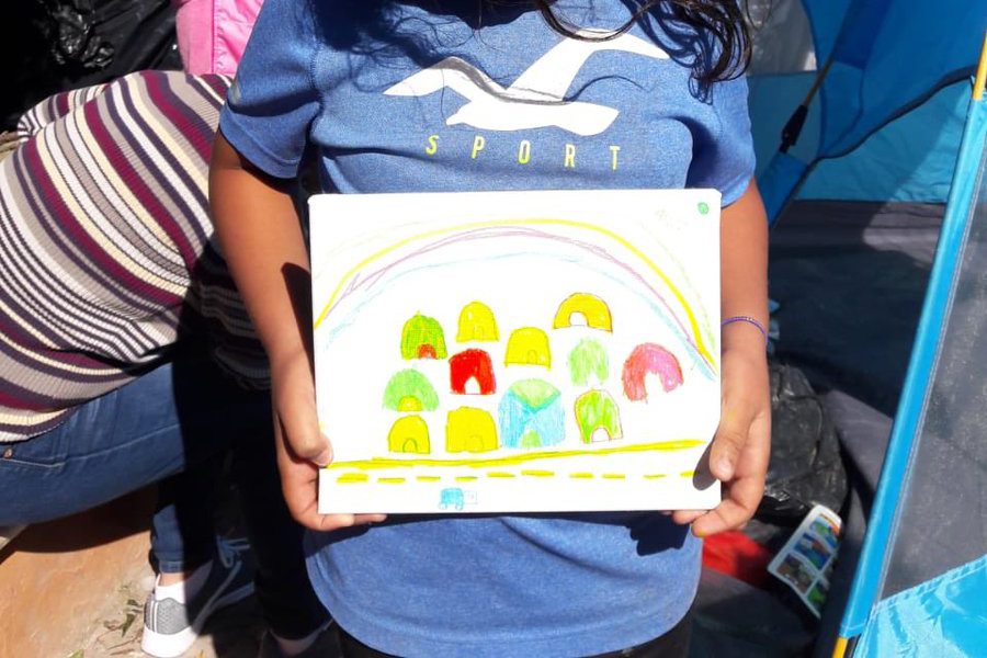A young girl holds up her drawing of the Matamoros tent encampment where she lives.