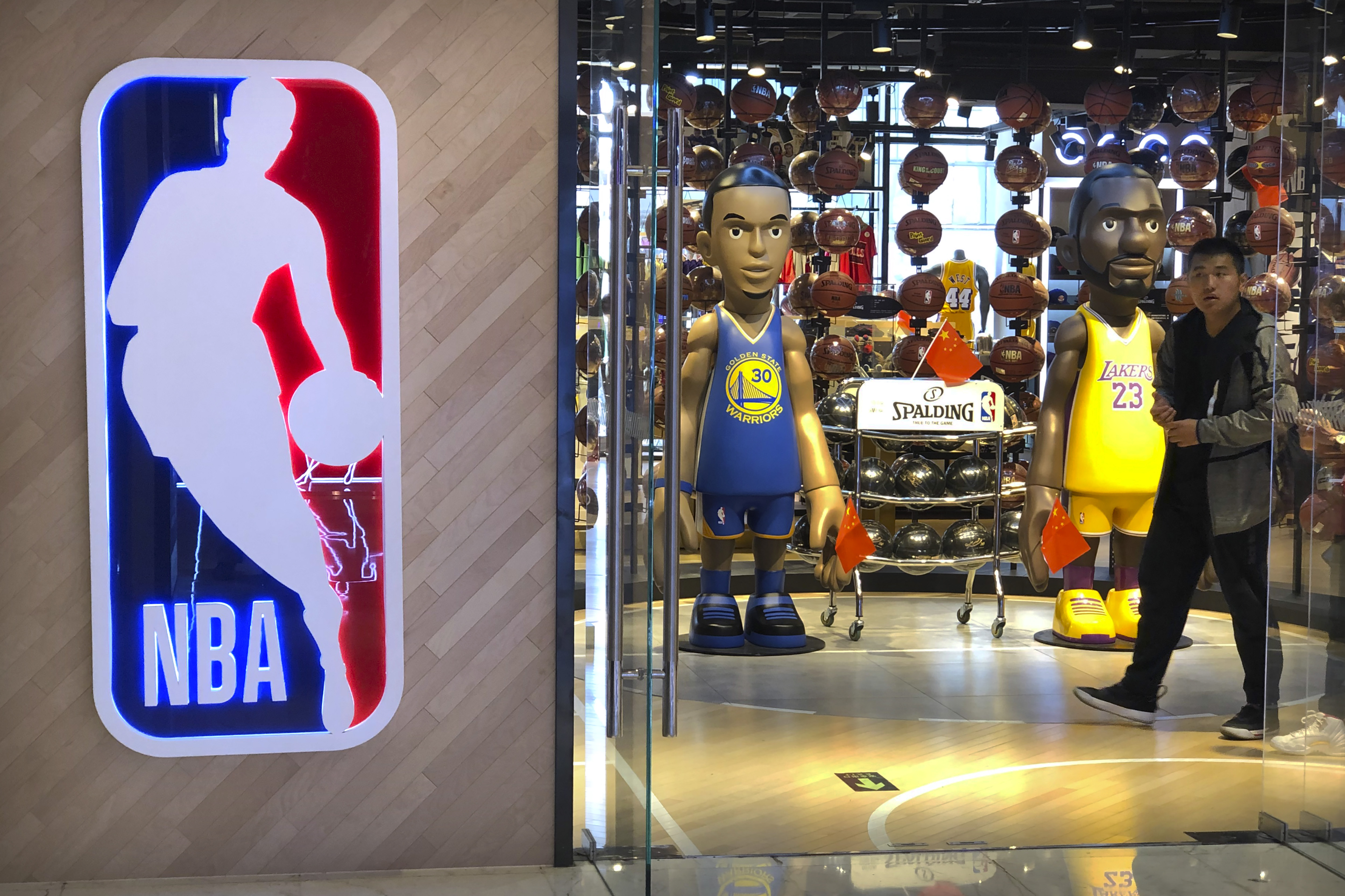 A man walks past statues of NBA players Stephen Curry of the Golden State Warriors, left, and Lebron James of the Los Angeles Lakers holding Chinese flags in the entrance of an NBA merchandise store in Beijing on Oct. 8, 2019.