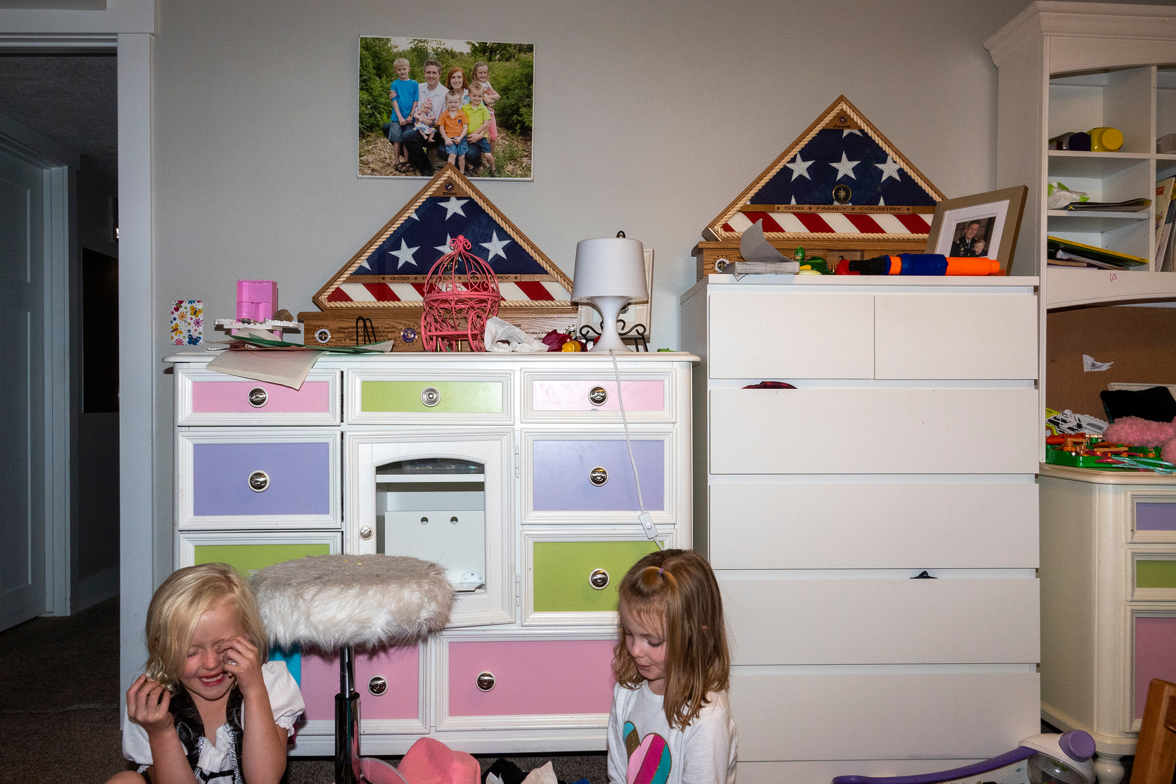 Ellie plays with cousin Vivian Pack in her bedroom. Resting on the dressers are two framed flags presented to each member of the family by the U.S. military.