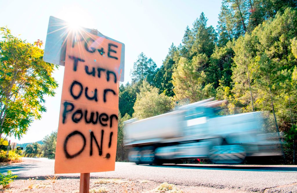 A sign calling for PG&E to turn the power back on is seen on the side of the road during a statewide blackout in Calistoga, California, on Oct., 10, 2019.