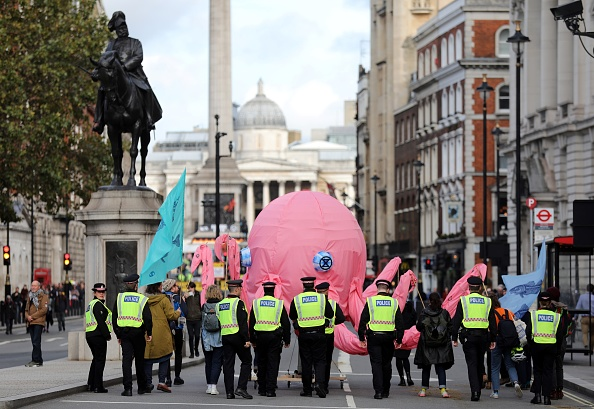 Activists carry a giant pink Octopus as they walk along Whitehall towards Trafalgar Square, followed by police officers, during the third day of climate change demonstrations by the Extinction Rebellion group in central London, on October 9, 2019.