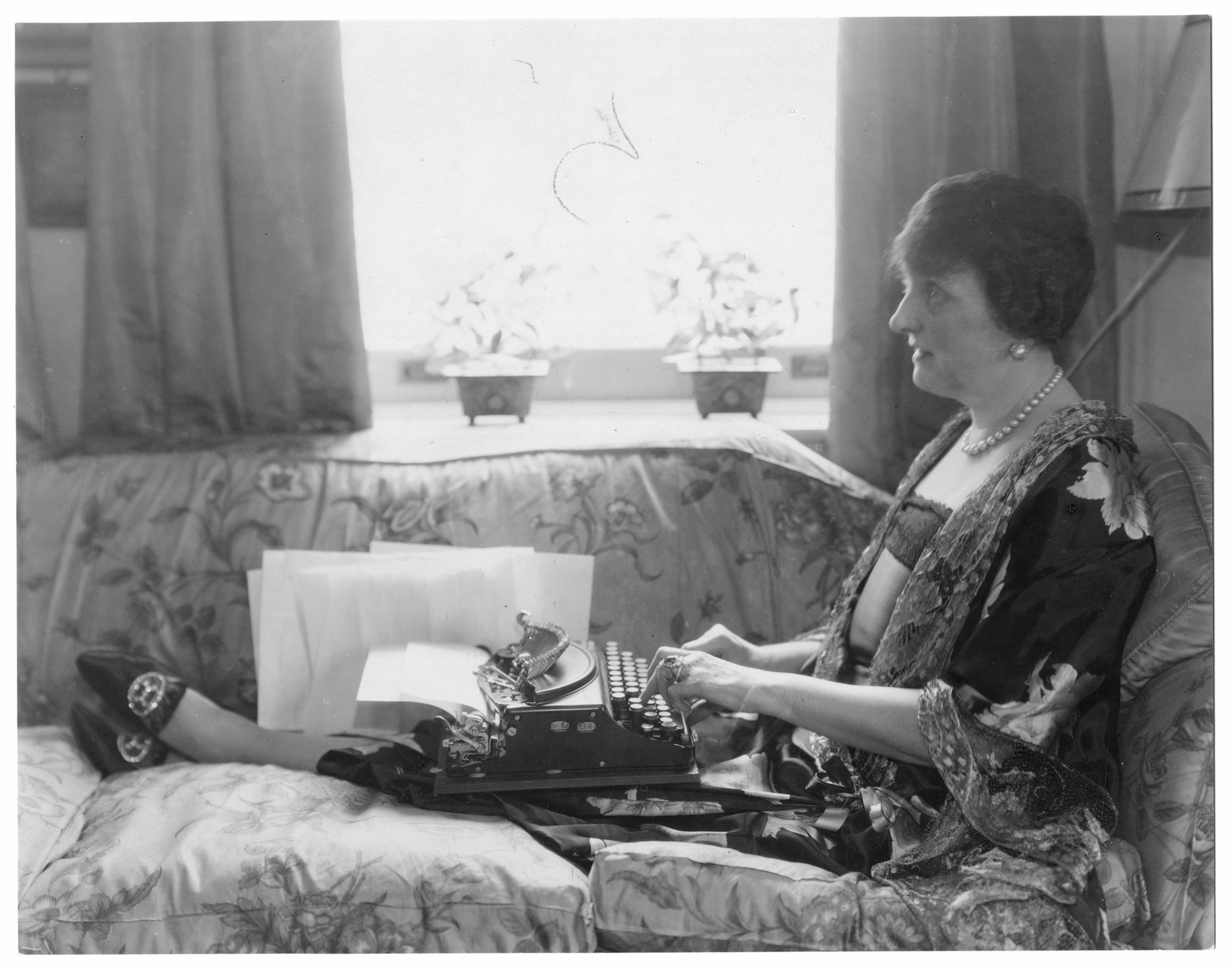 Etiquette author Emily Post, in pearls and flowing robe, sitting lengthwise on couch with legs stretched out, typewriter in her lap, 1927.