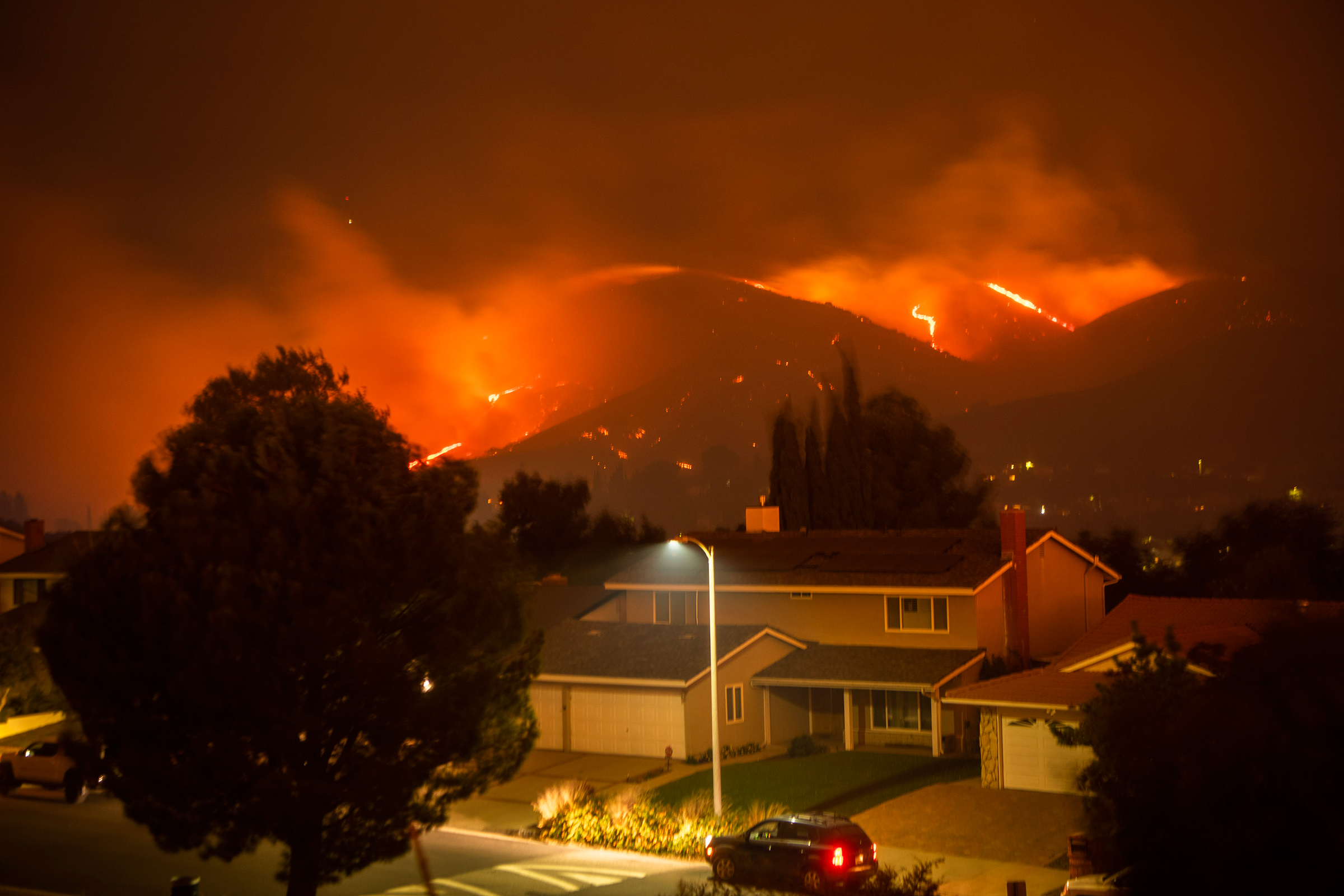 The Saddleridge Fire burns through and above Porter Ranch, Calif., early on Oct. 11, 2019.