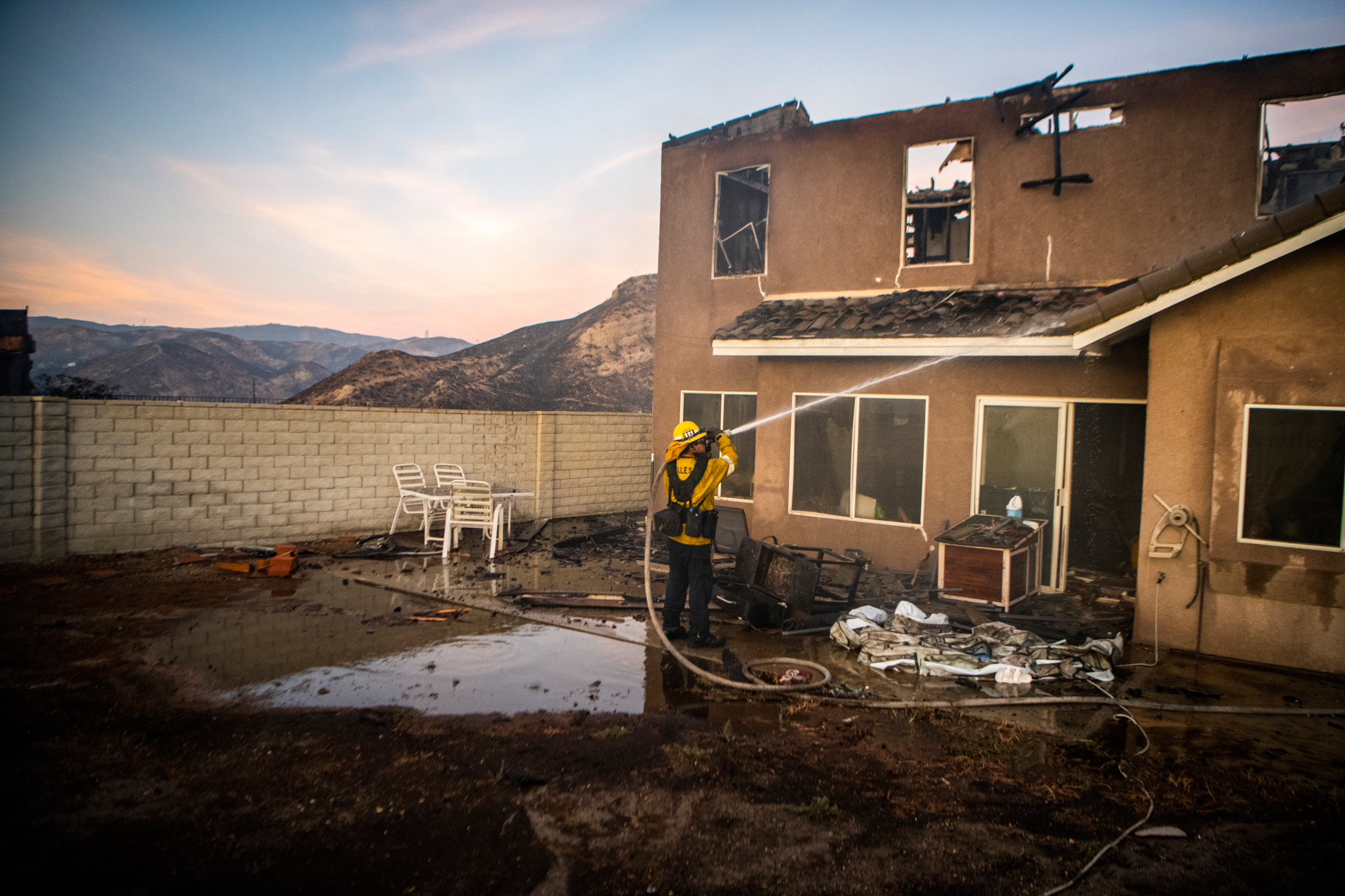 A firefighter hoses down a damaged house as the Tick Fire burns in the Santa Clarita, Calif., area on Oct. 24, 2019.