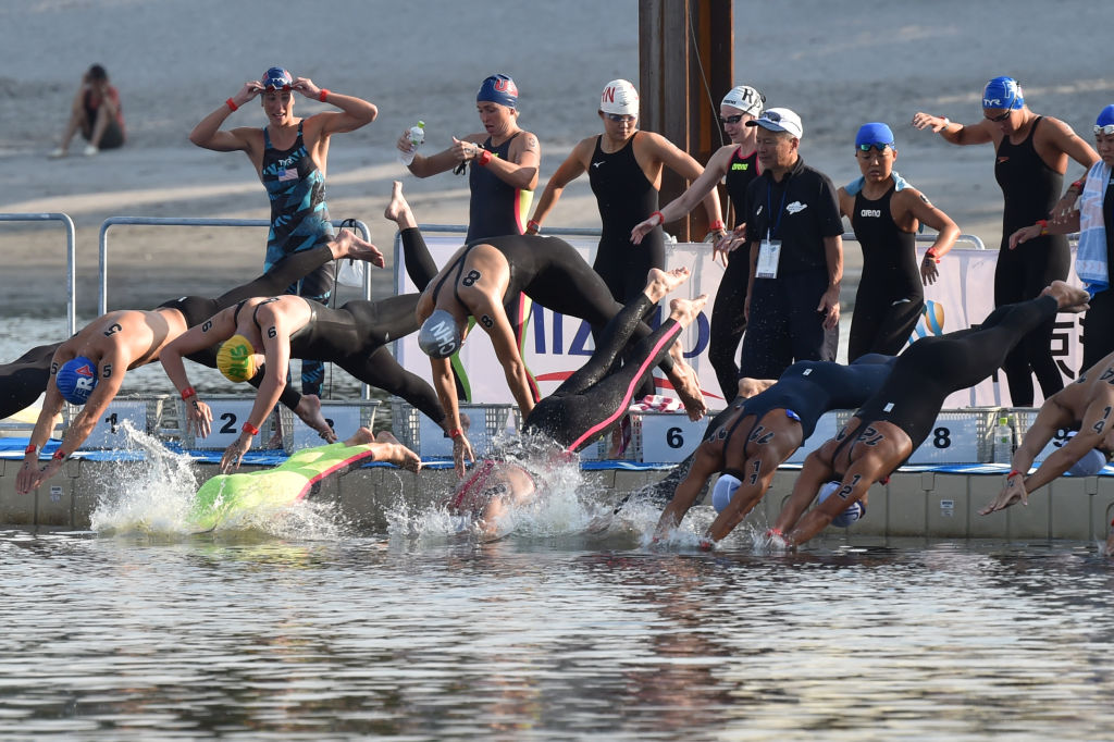 Swimmers dive into the sea at the start of the men's Marathon Swimming 5km competition, as a test event for Tokyo 2020 Olympic Games at Odaiba Marine Park in Tokyo on August 11, 2019.