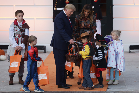 U.S. President Donald Trump and first lady Melania Trump hand out candy to children as they trick-or-treat during a Halloween at the White House event at the South Portico of the White House in Washington, DC on October 28, 2019.