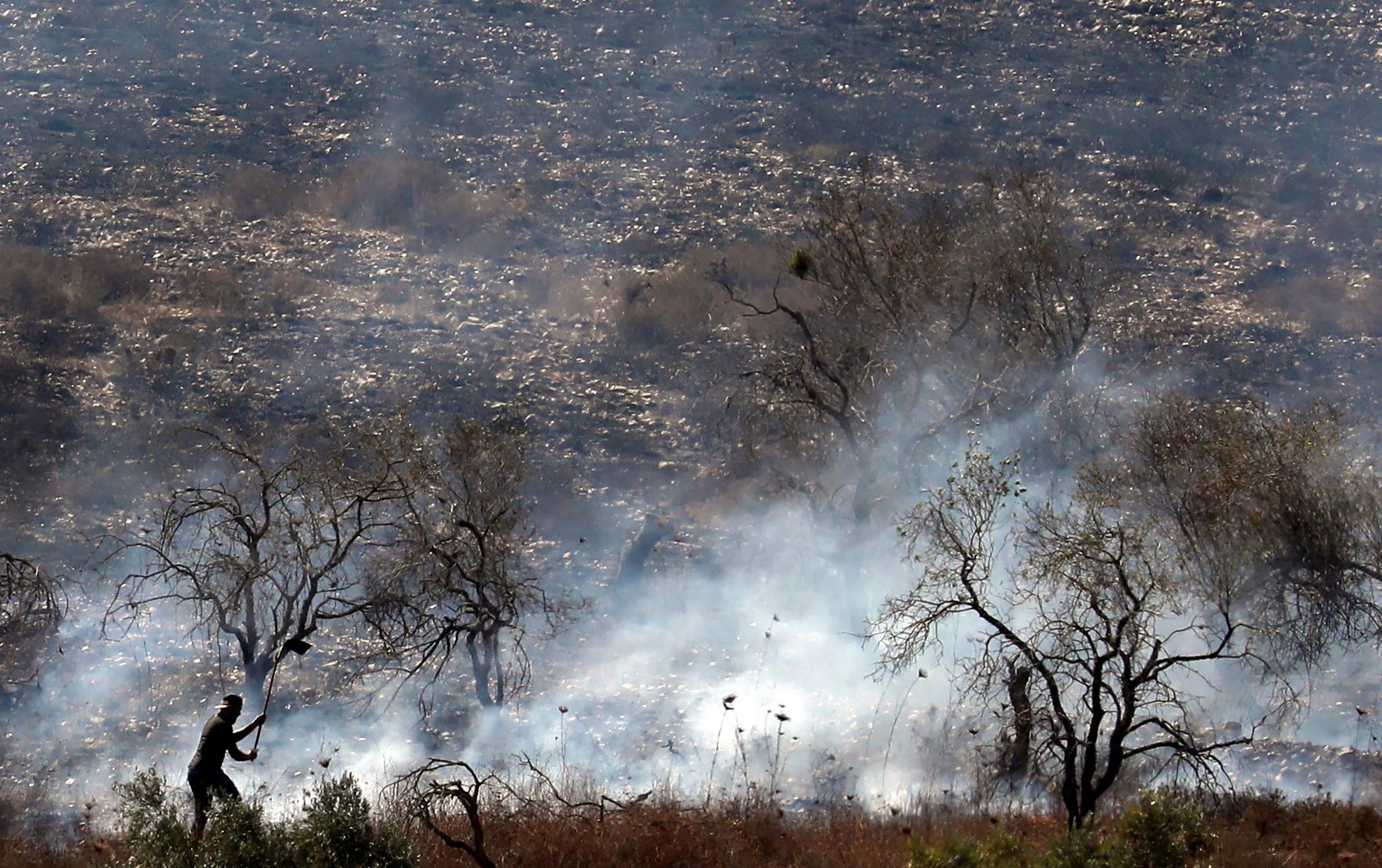 A Palestinian tries to extinguish a fire in an olive grove near the Palestinian village of Burin in the northern West Bank by the Israeli settlement of Yitzhar, on Oct. 16, 2019.