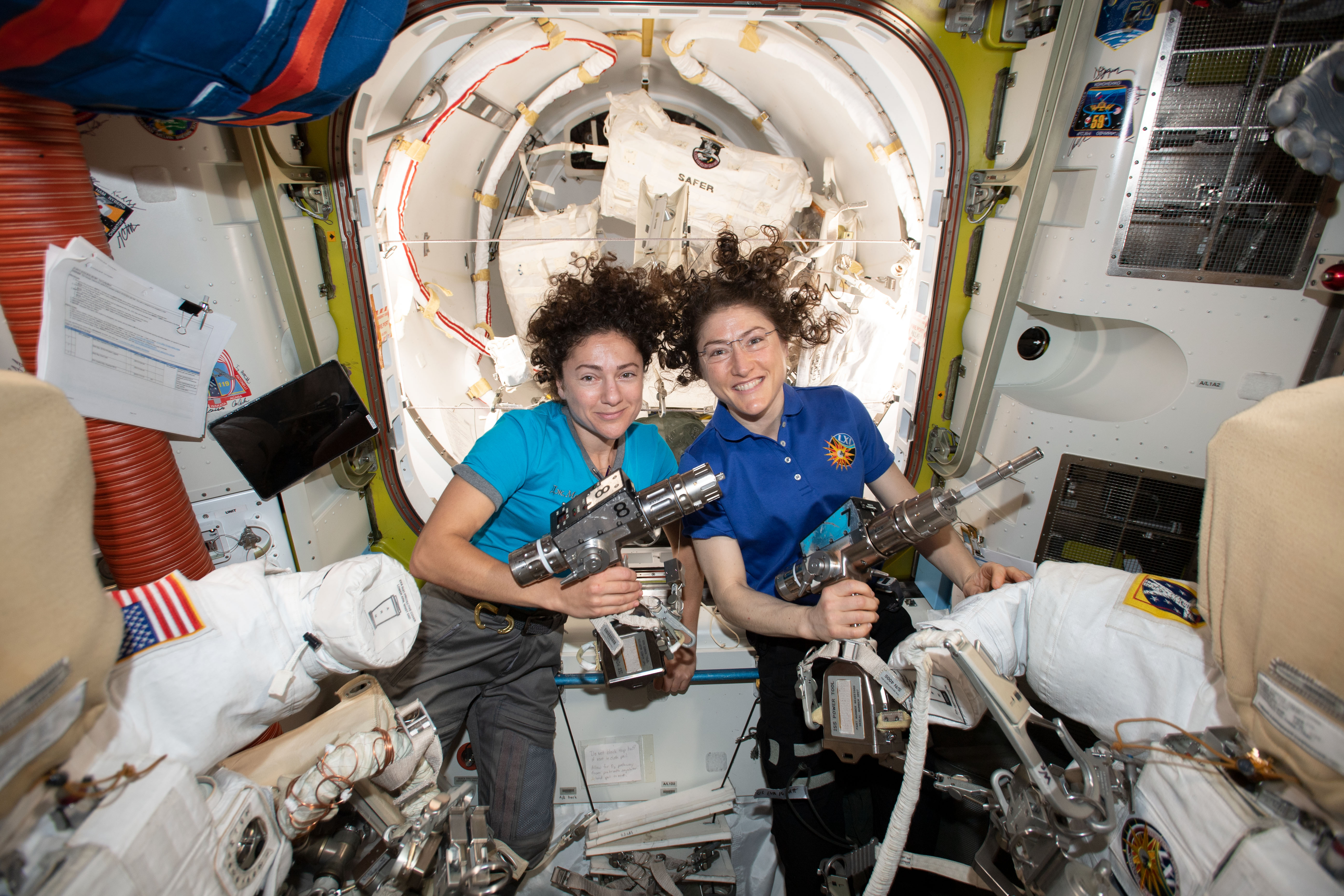 NASA astronauts Jessica Meir (left) and Christina Koch inside the Quest airlock preparing the U.S. spacesuits and tools they will use on their first spacewalk together.