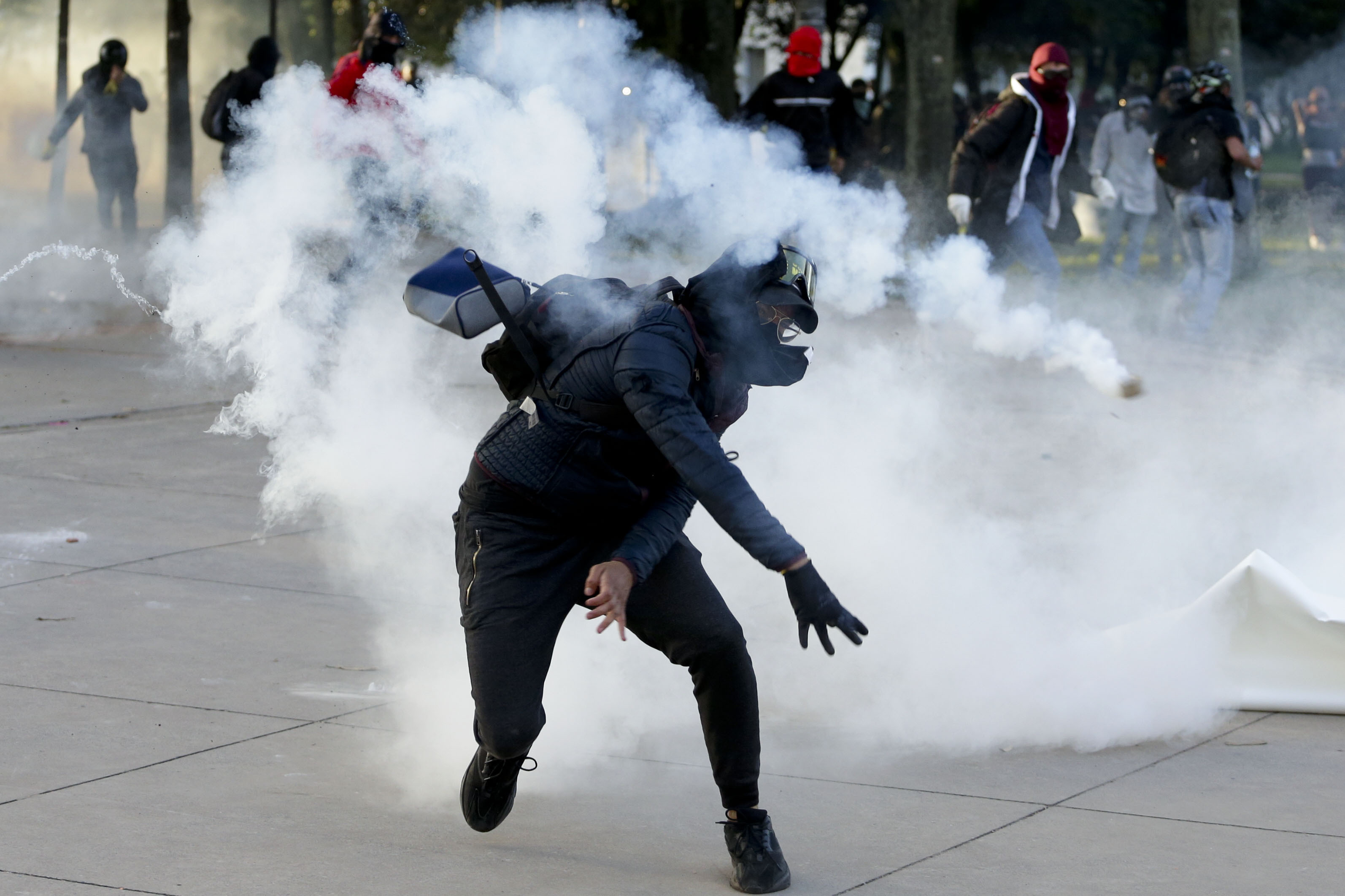 A student throws a tear gas canister back at the police during clashes at the National University in Bogota, Colombia, Tuesday, Nov. 26, 2019.